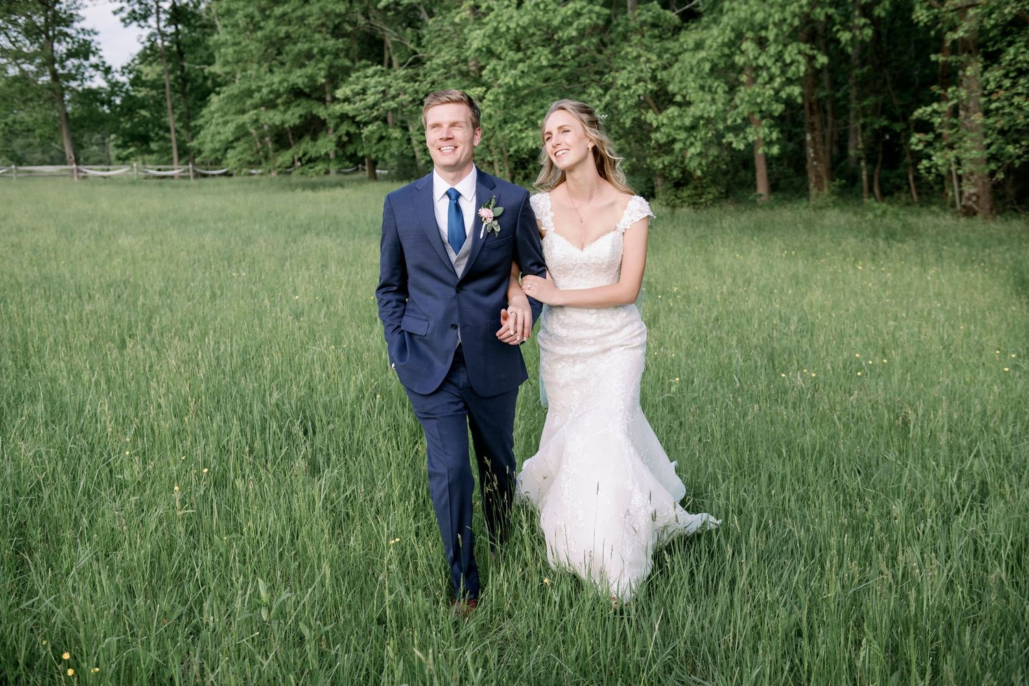 bride and groom walking in field after backyard farm wedding