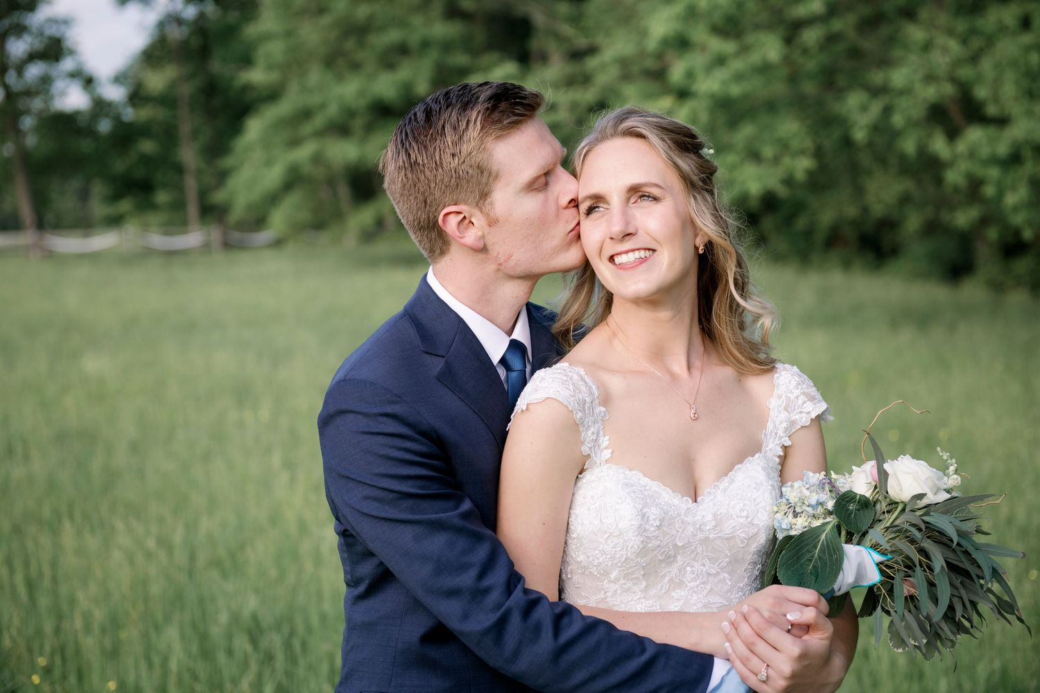 groom kisses bride on cheek after backyard farm wedding
