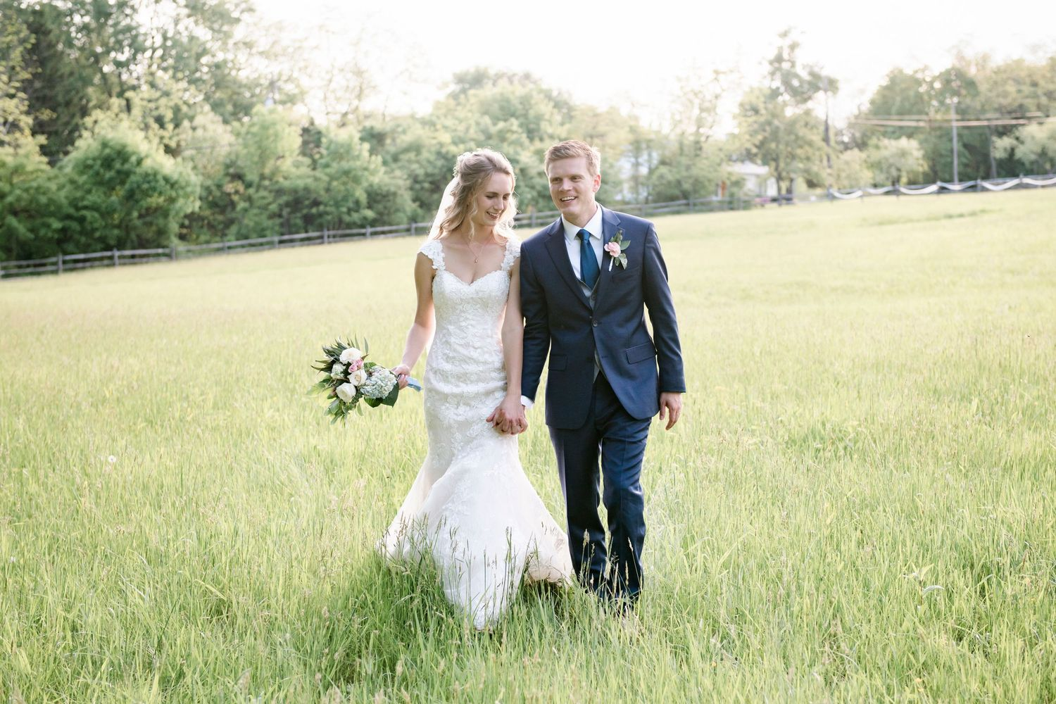 bride and groom walking in tall grass after backyard farm wedding