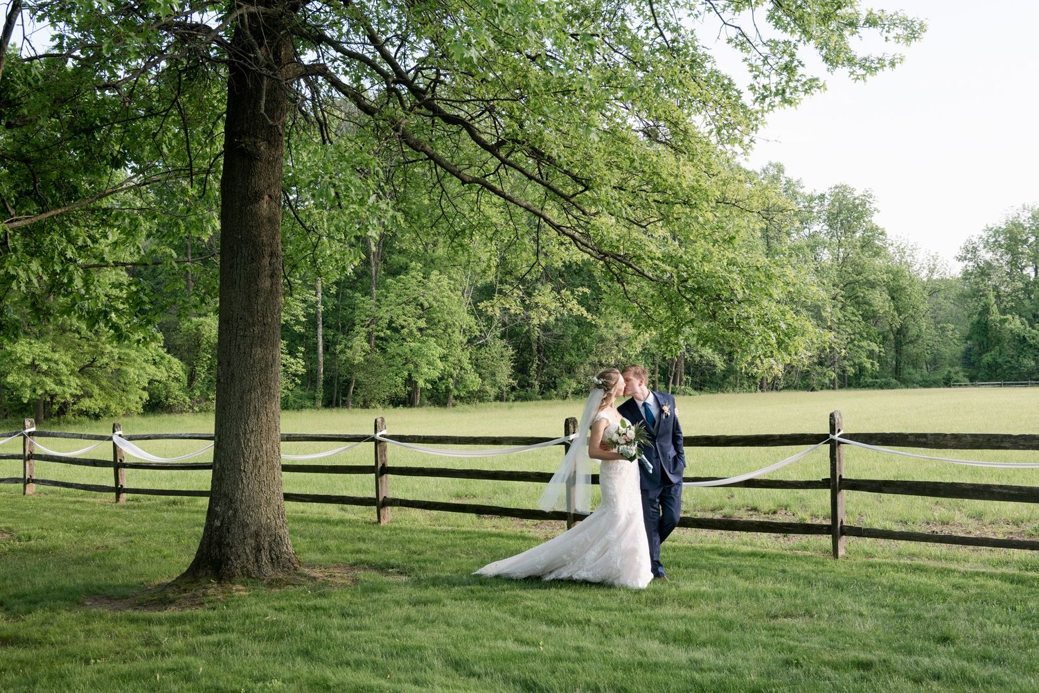 bride and groom walking by farm fence after backyard farm wedding