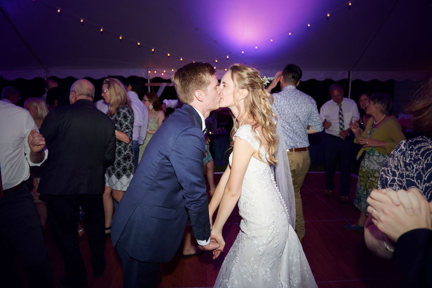 bride and groom kiss during reception of backyard farm wedding
