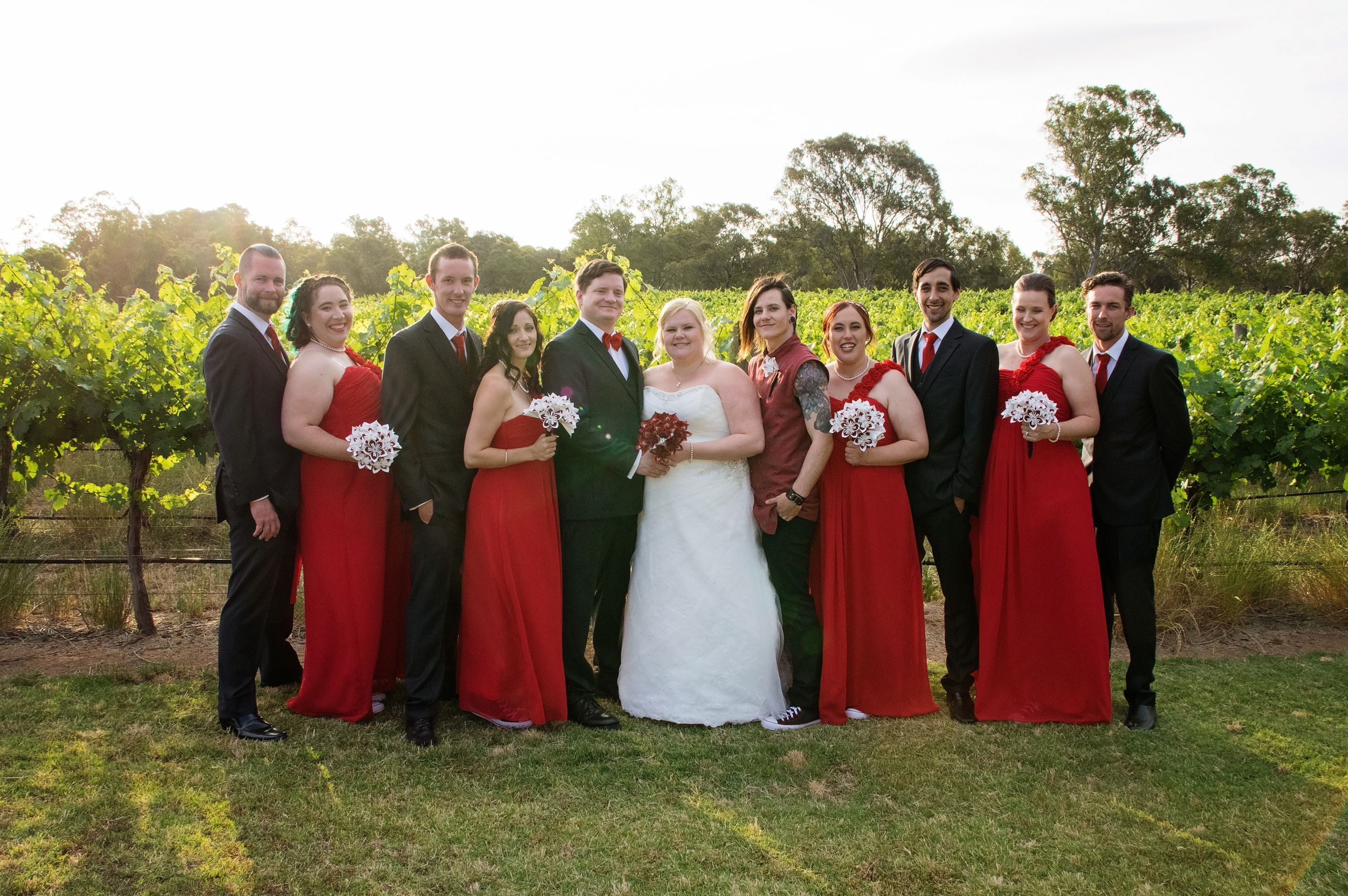 bridal party in red and black posing with bride and groom in wineyard