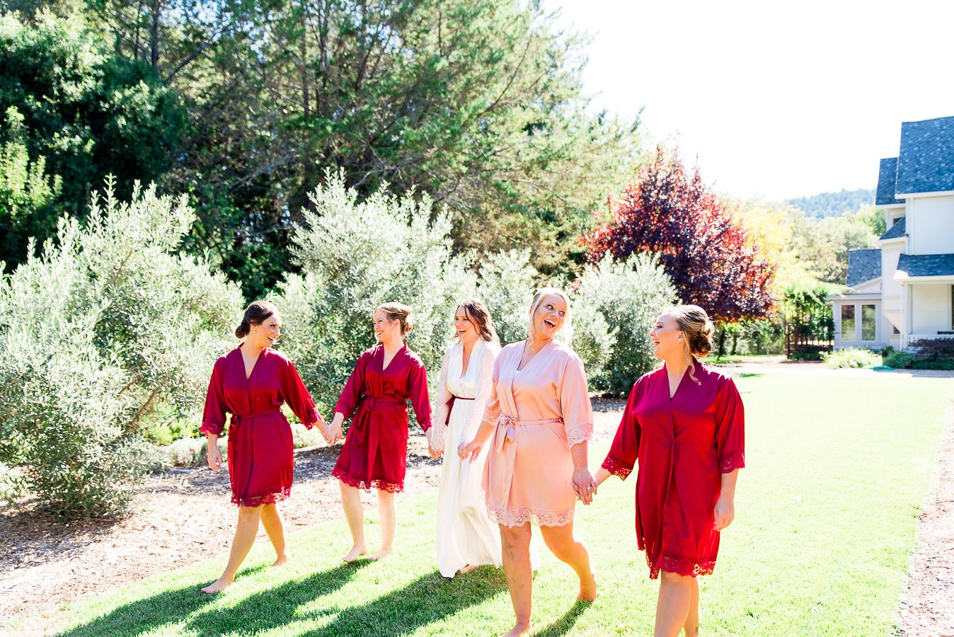 bridesmaids in red and blush robes walking in yard in California AirBNB