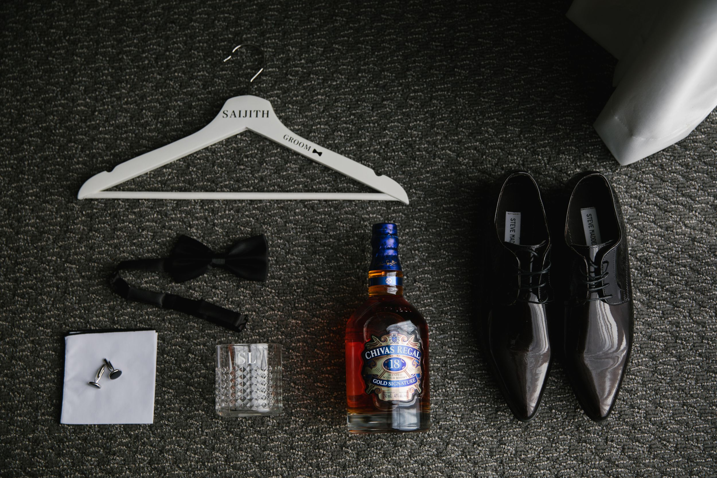 flat lay of groom details, hanger, bow tie, whiskey bottle and shoes