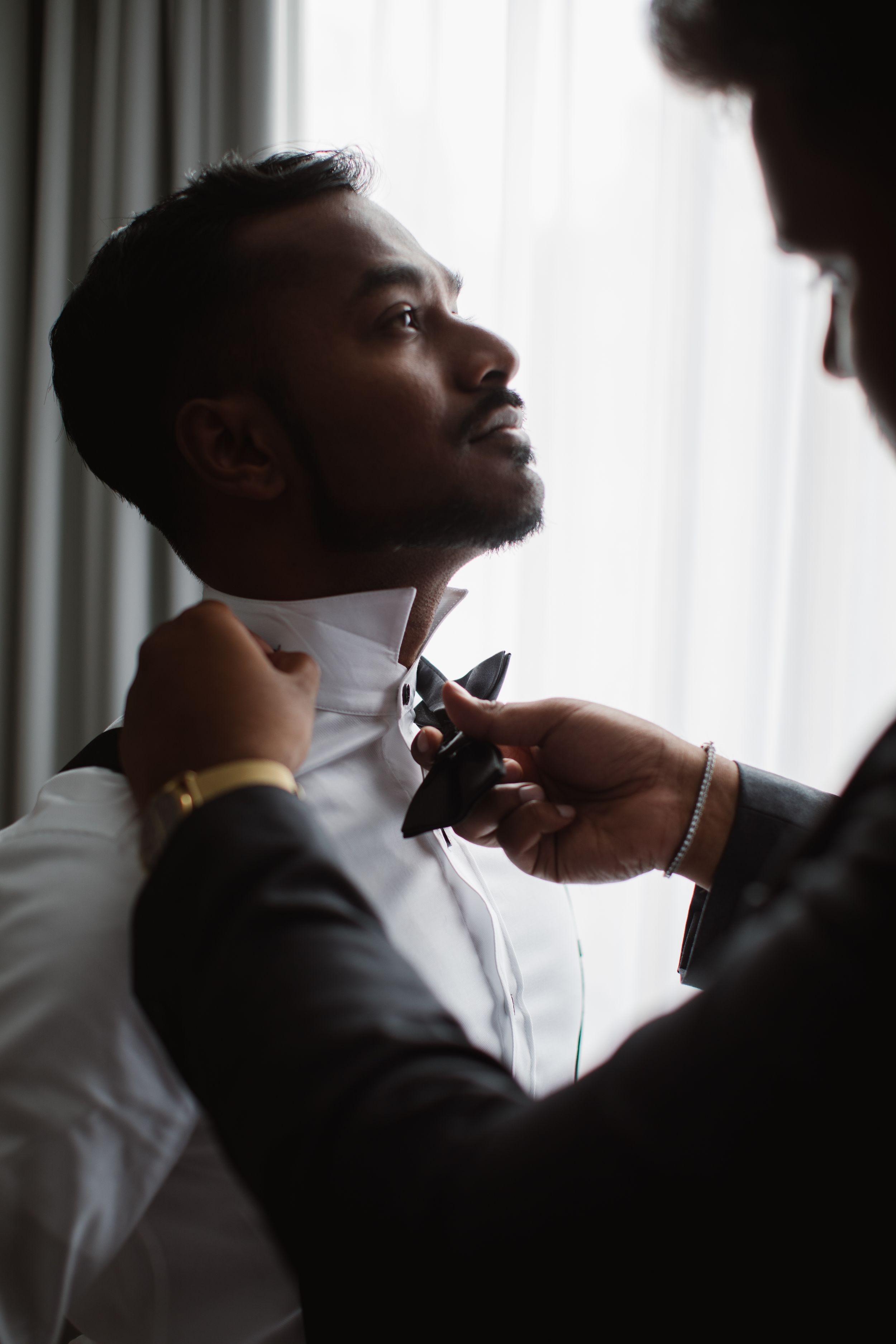 groomsman helping groom tie his bowtie