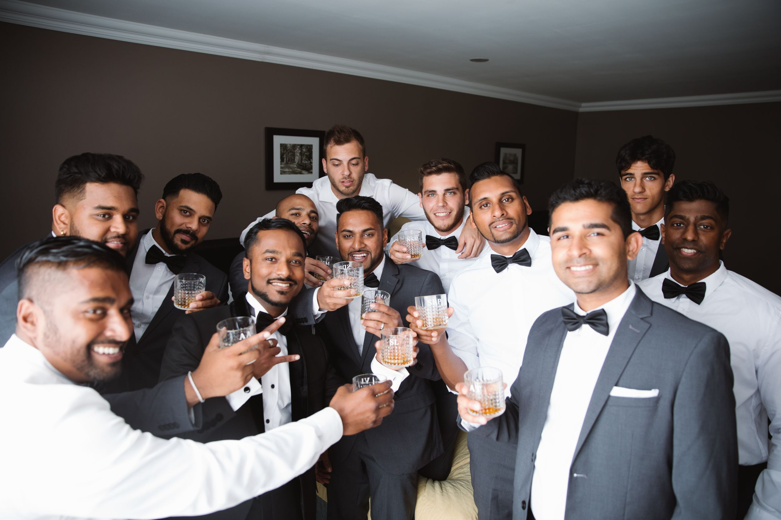 groomsmen cheersing glasses of whiskey