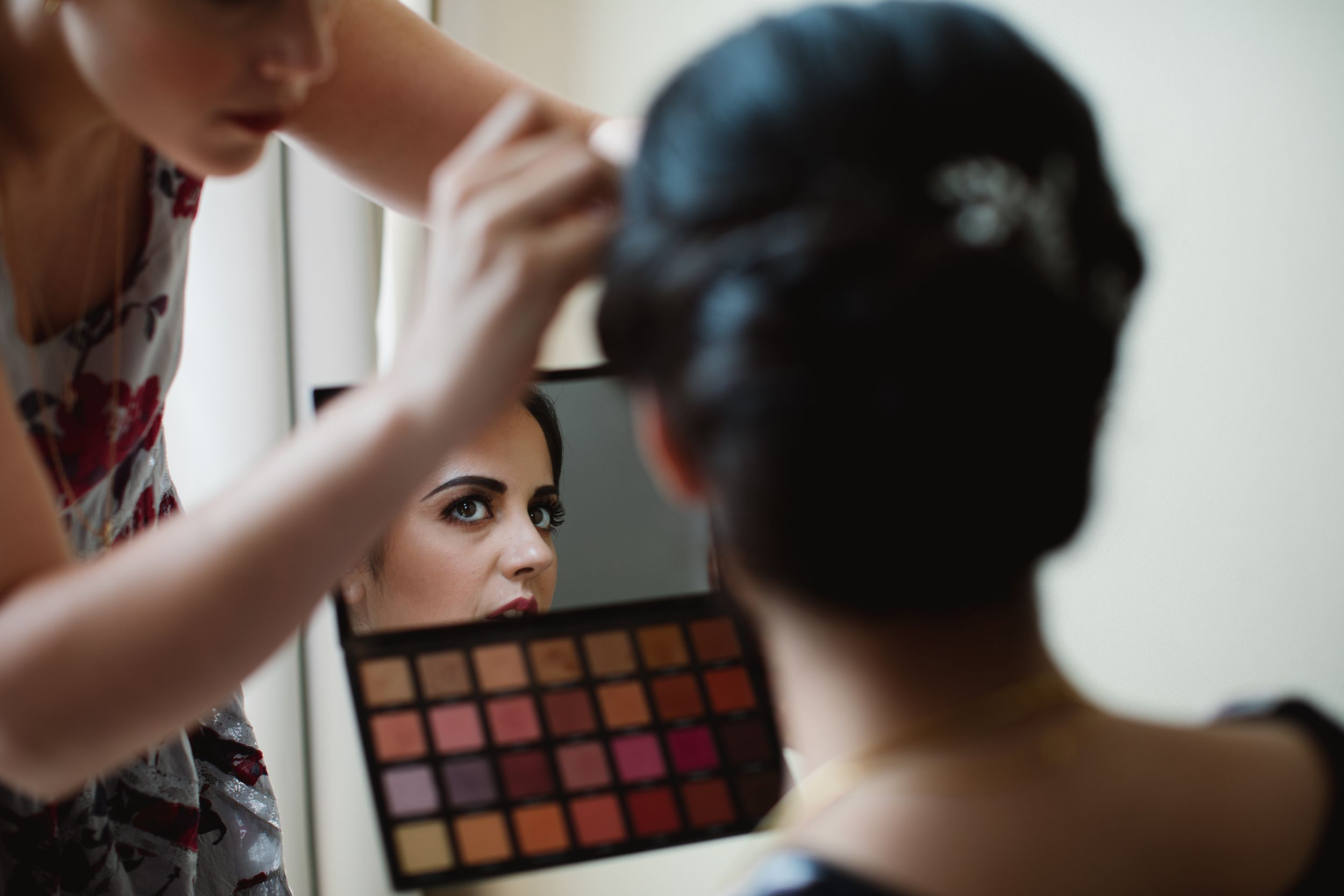 bride looking into mirror of a makeup palette