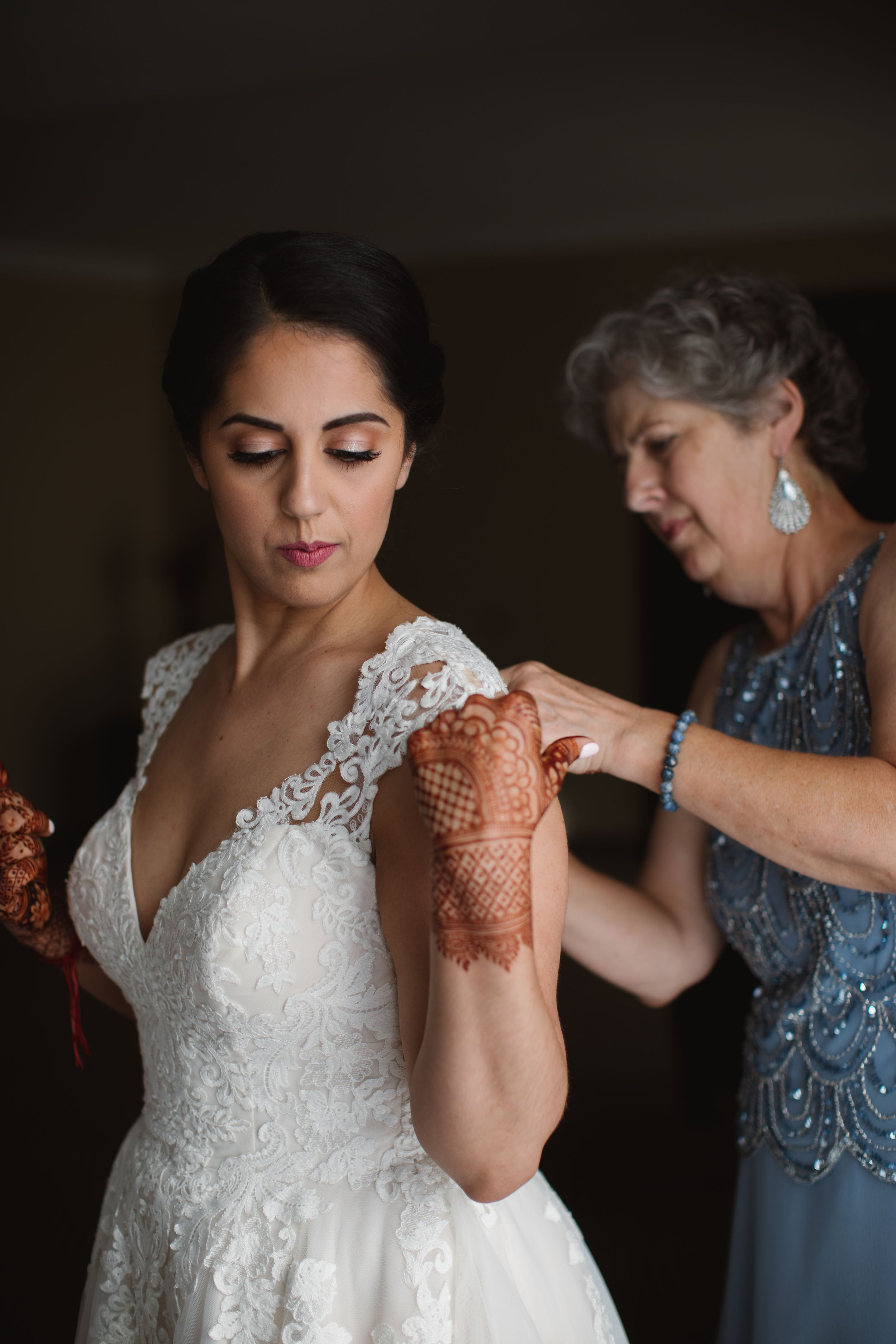 bride getting into her wedding dress and mom helping