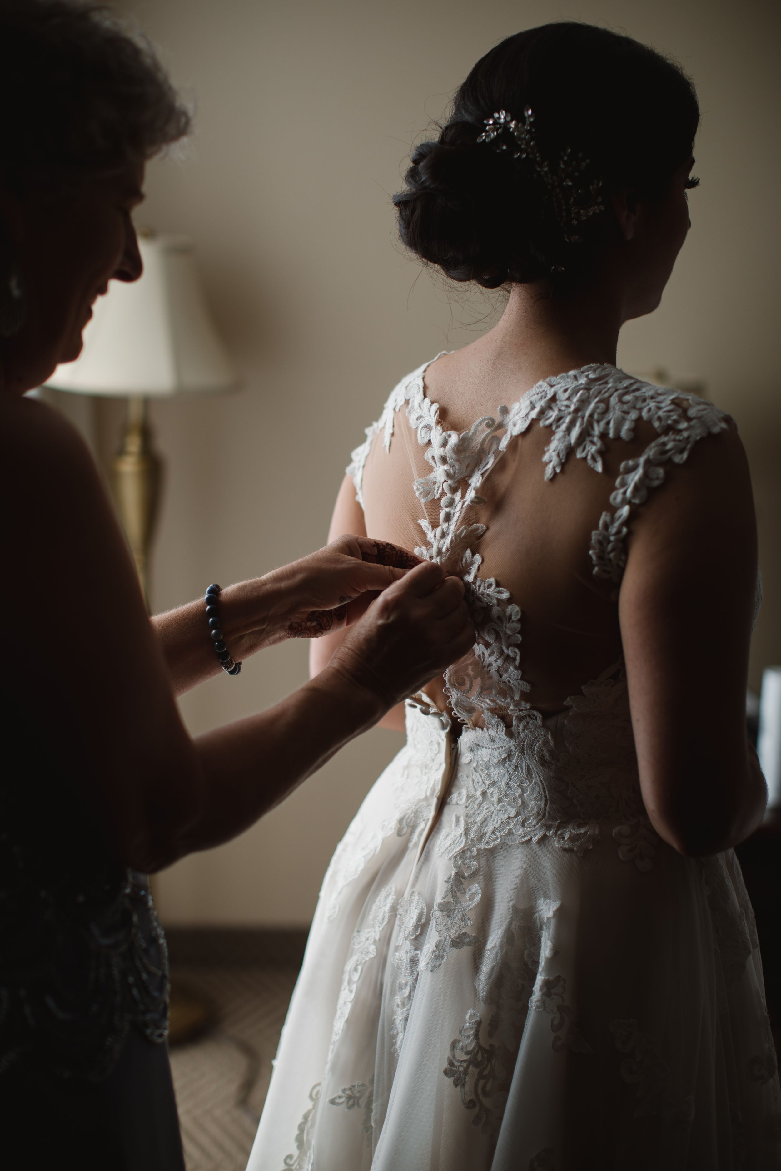 mom fastening buttons on a wedding dress