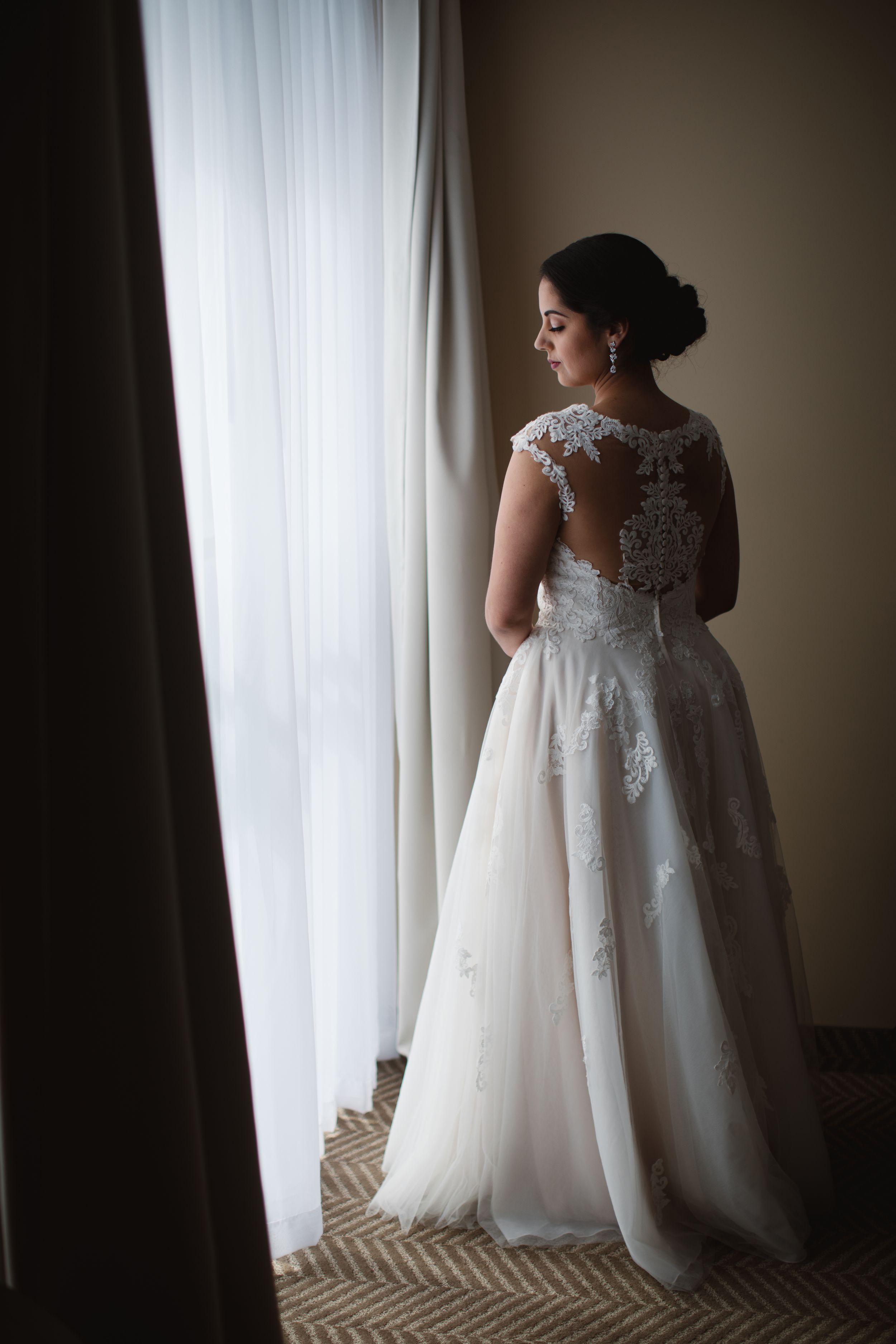 bride in wedding dress standing next to a window