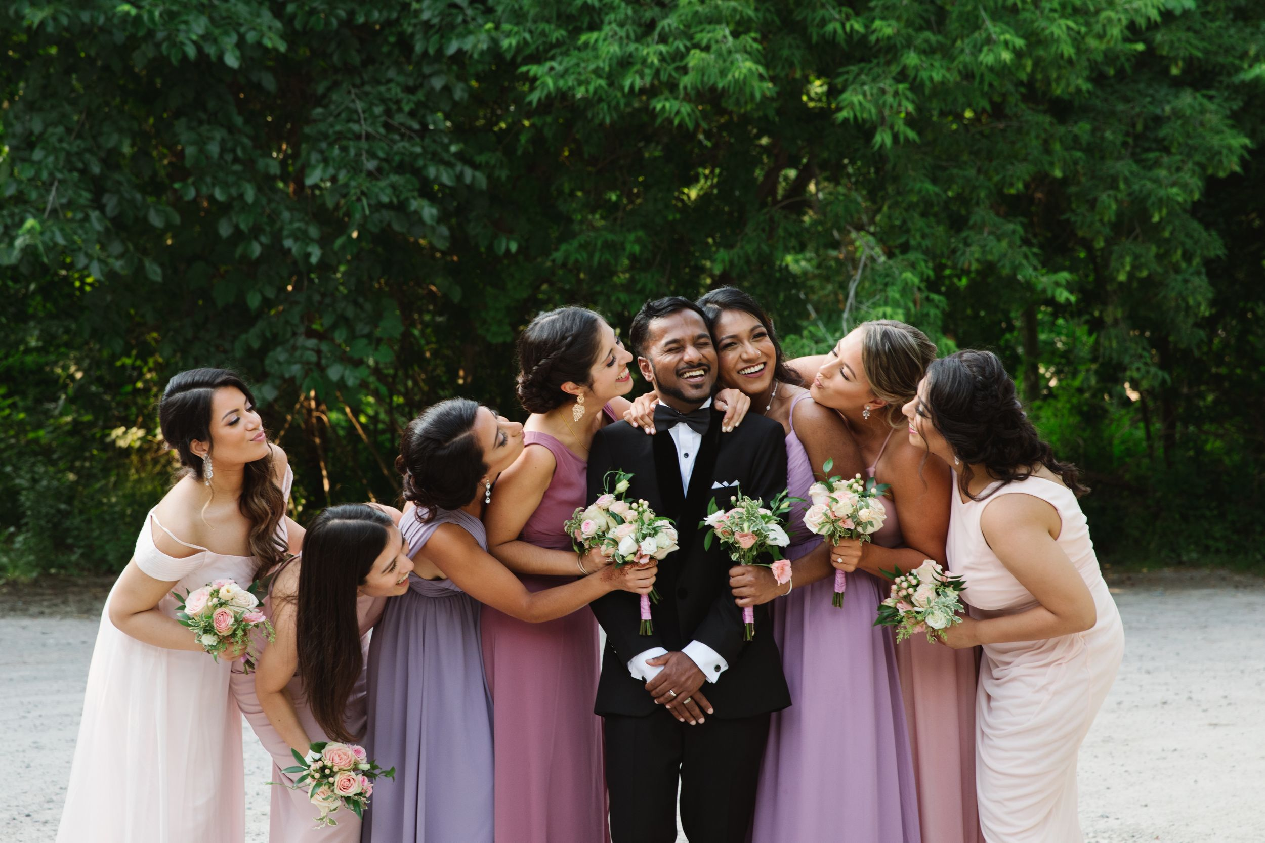bridesmaids kissing groom at rouge park