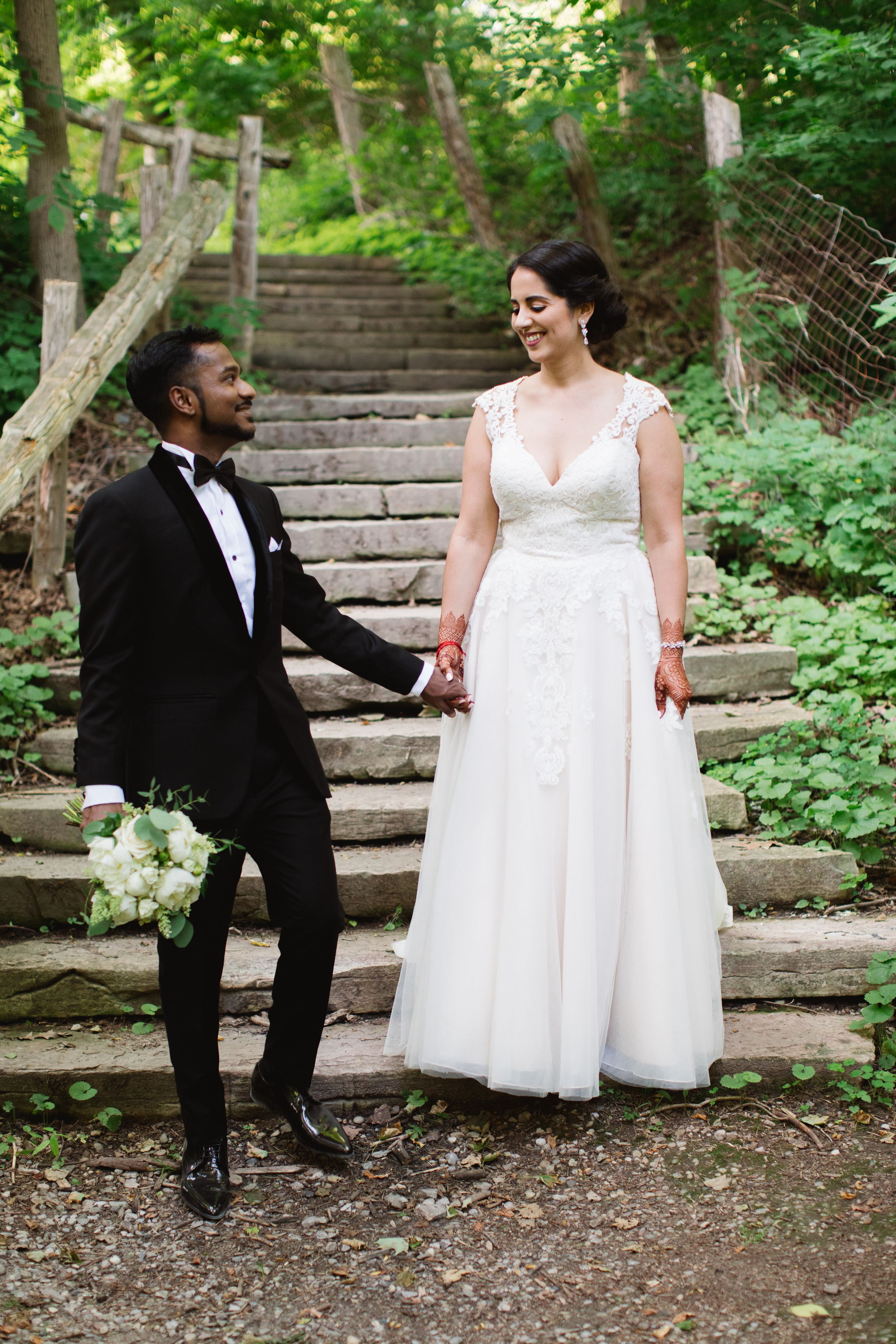 bride and groom looking at each other smiling on stairs in forest