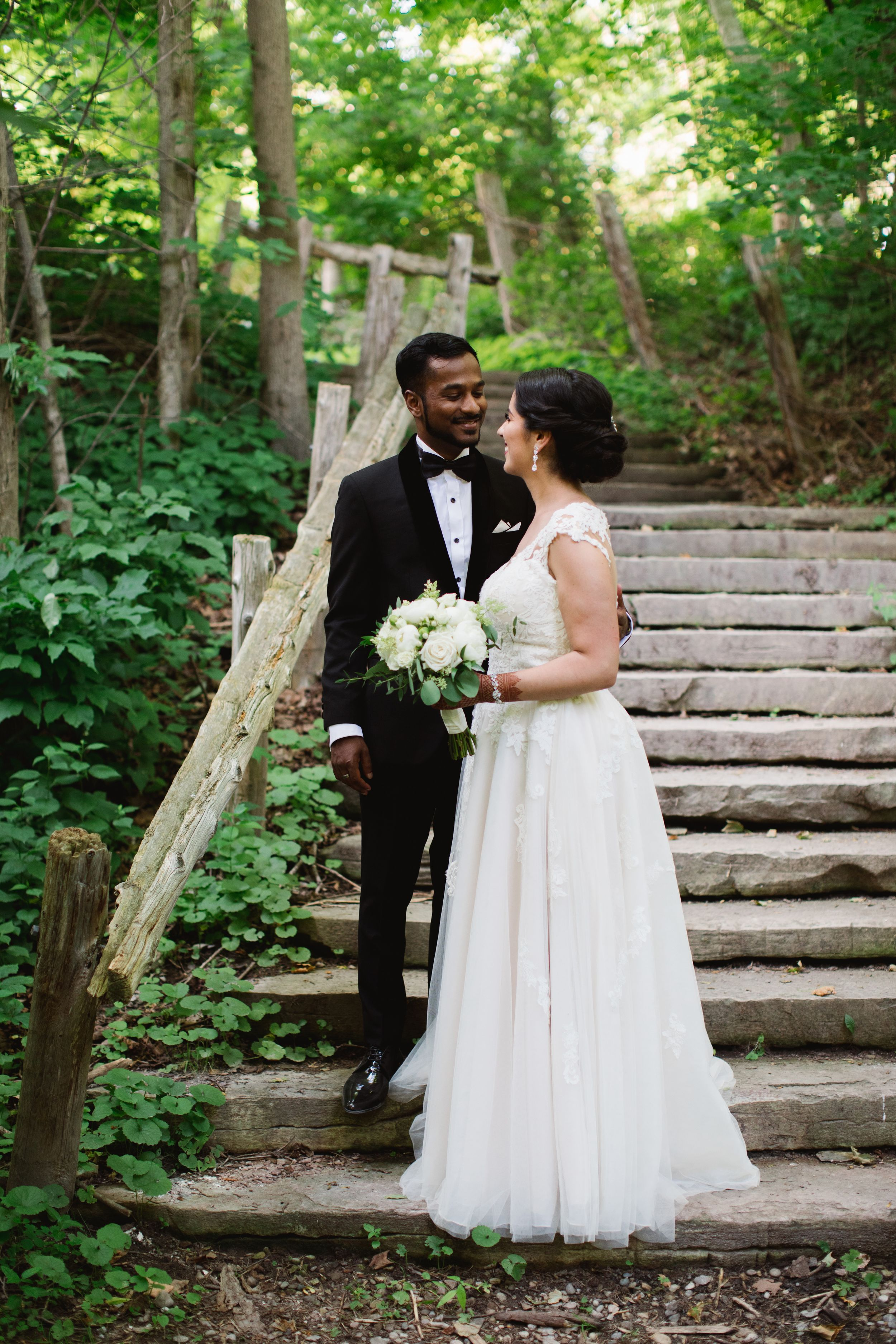 bride and groom close together in forest stairs