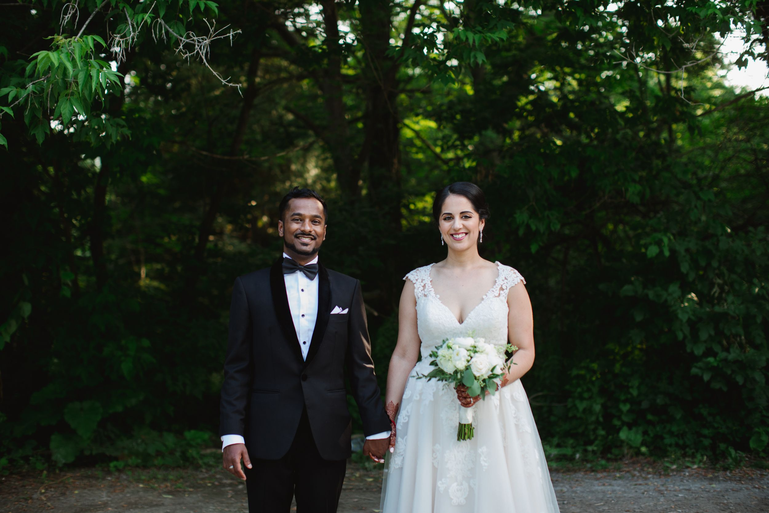 bride and groom holding hands facing the camera in park in toronto
