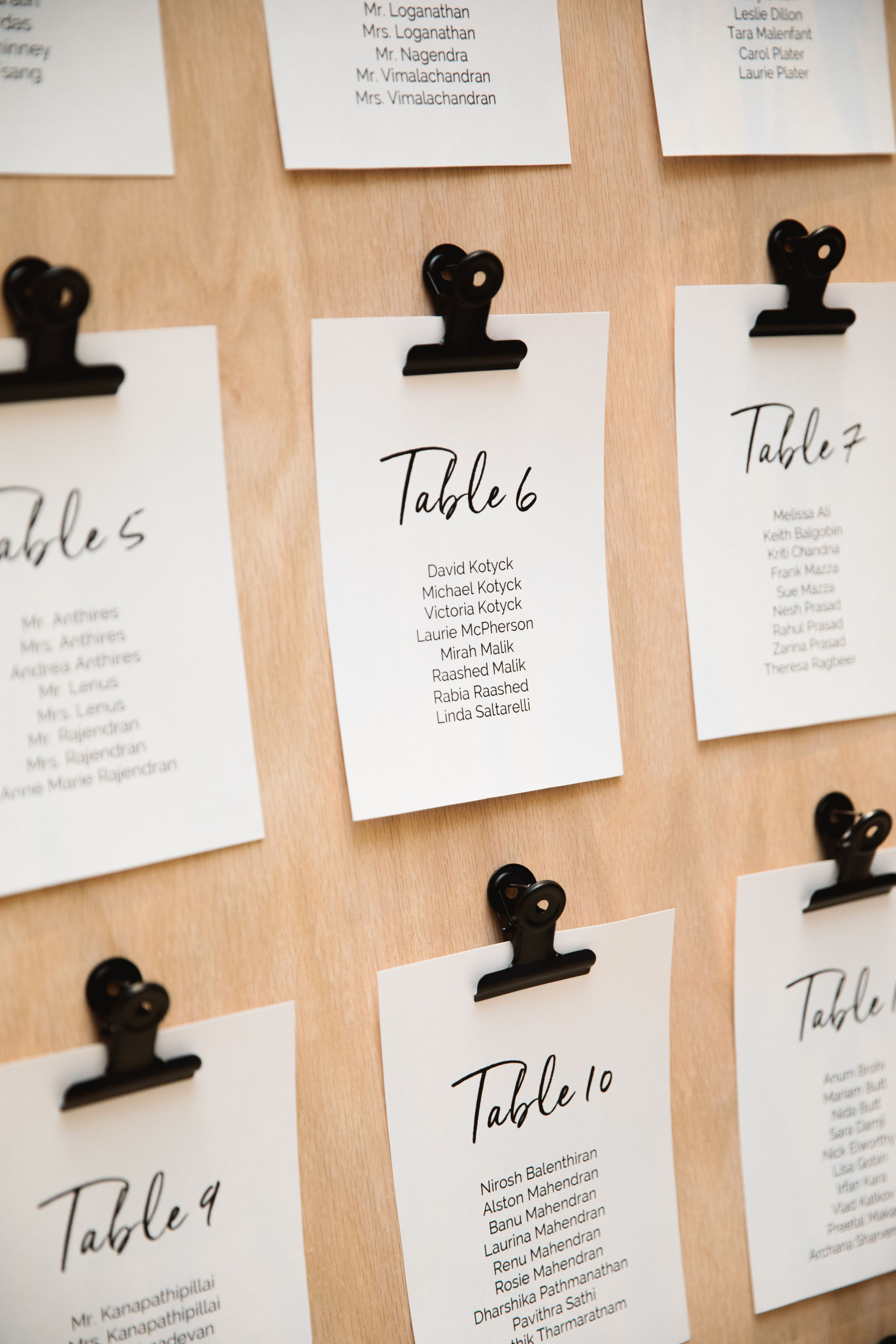 close up of seating chart on wood held by bulldog clips