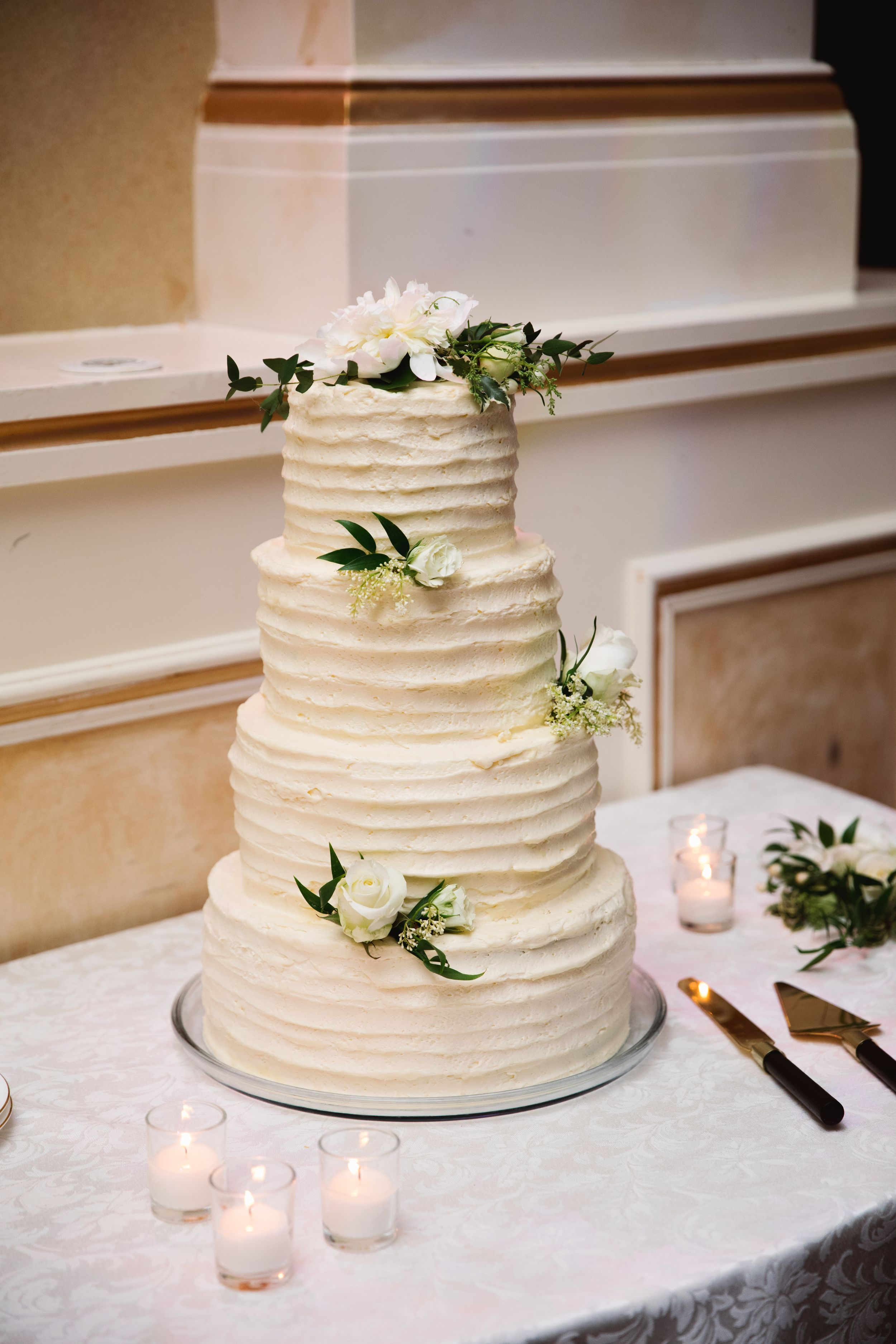 white wedding cake with greenery and candles around it