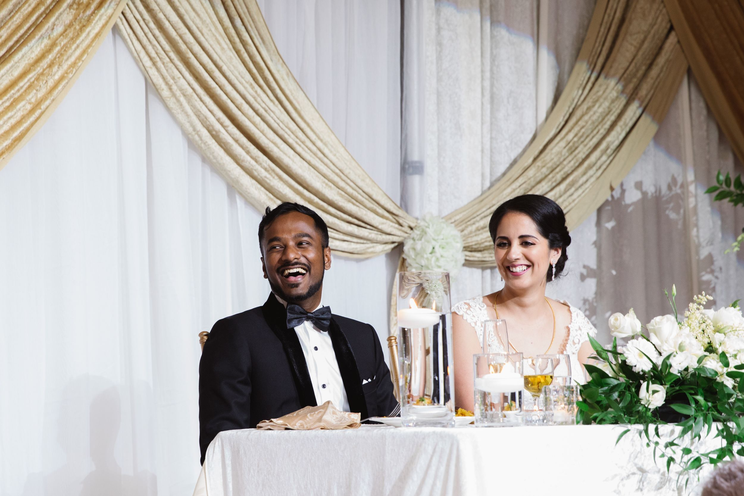 bride and groom sitting at a table laughing
