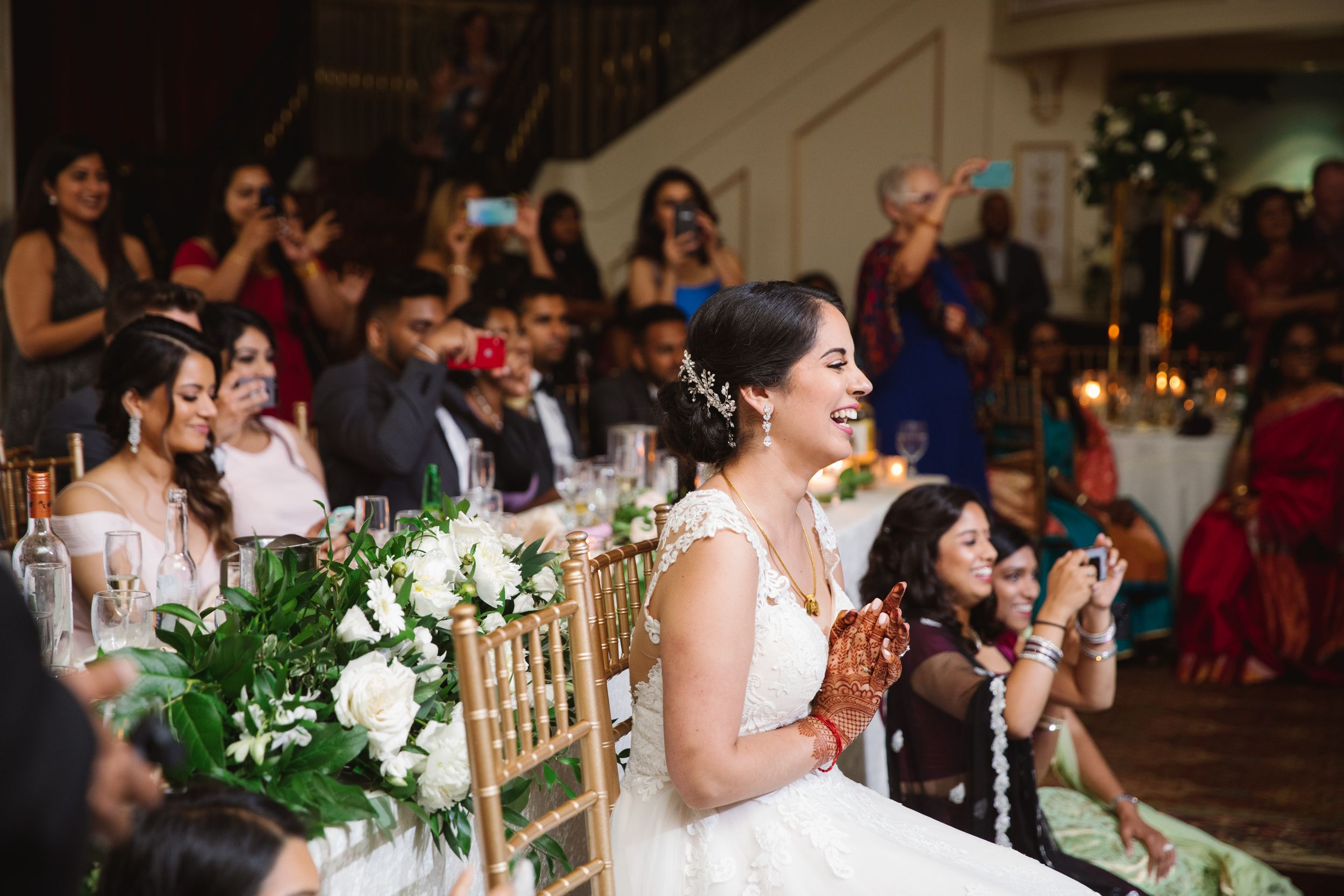 bride laughing and clapping on a chair with greenery behind