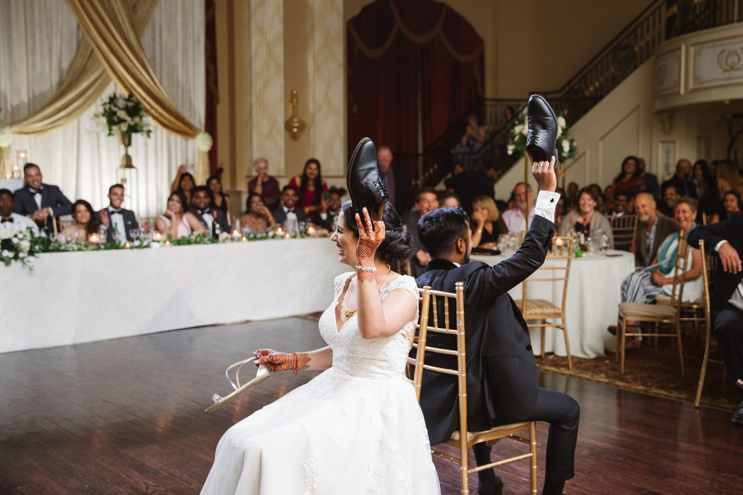 bride and groom shoe game holding up shoes during wedding reception