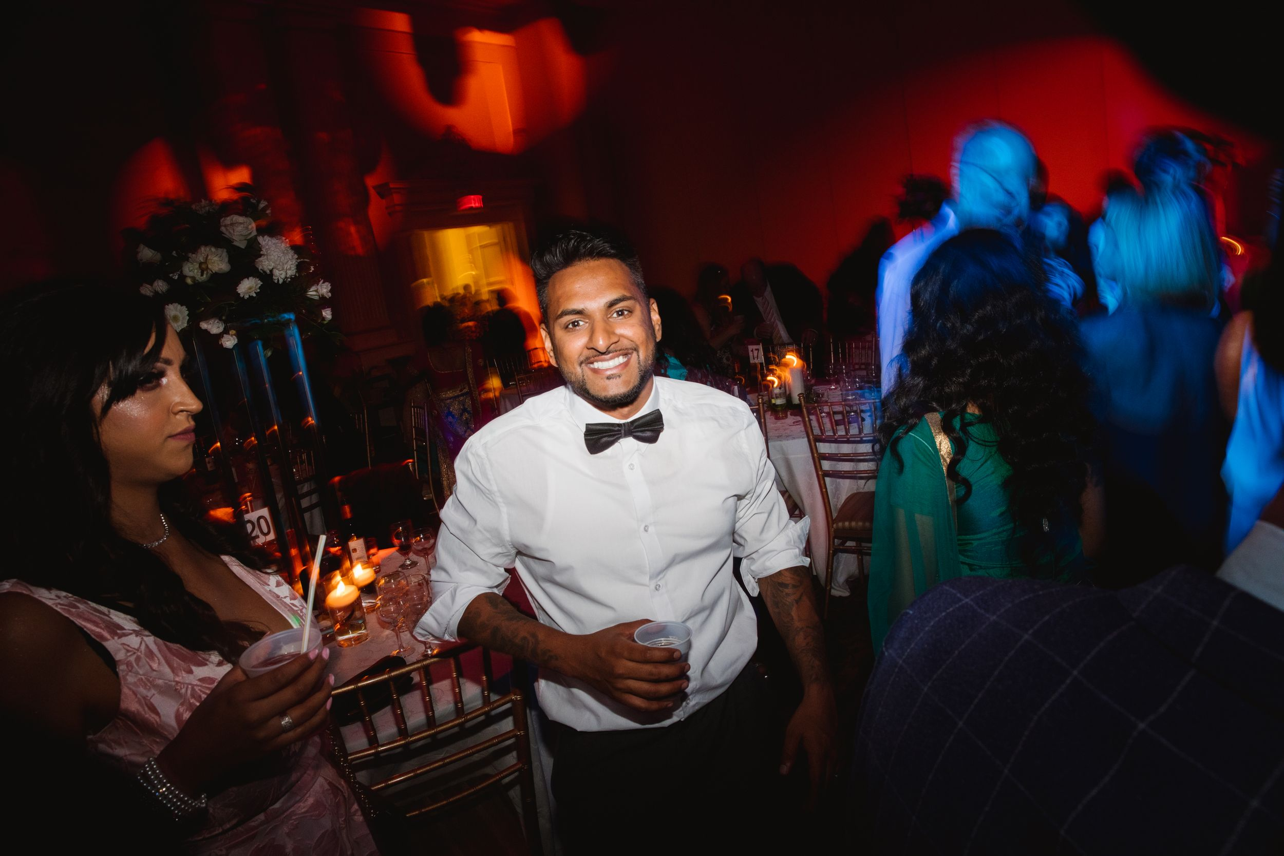 wedding party time groomsman smiling holding a drink