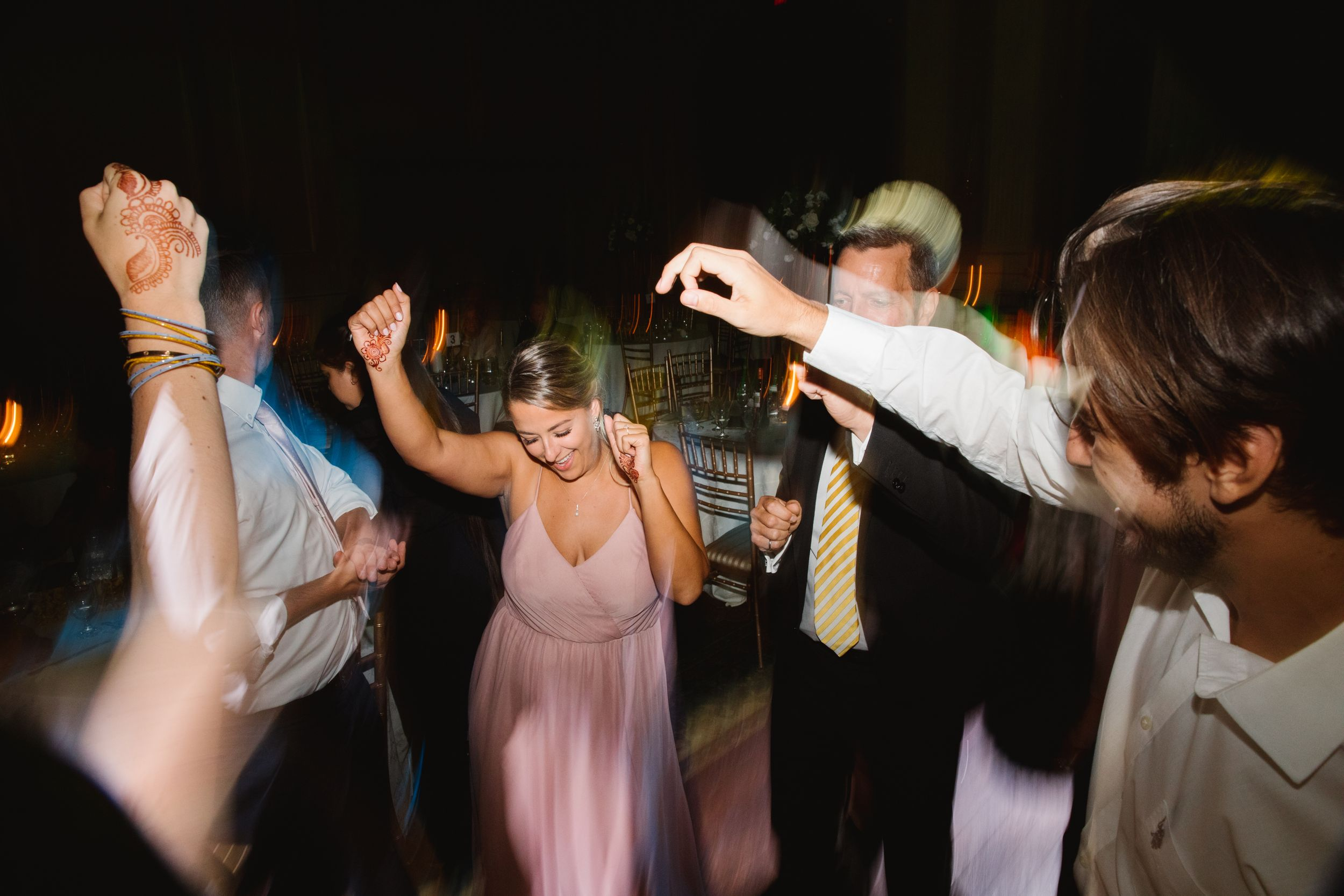 wedding party guests dancing hands up in the air