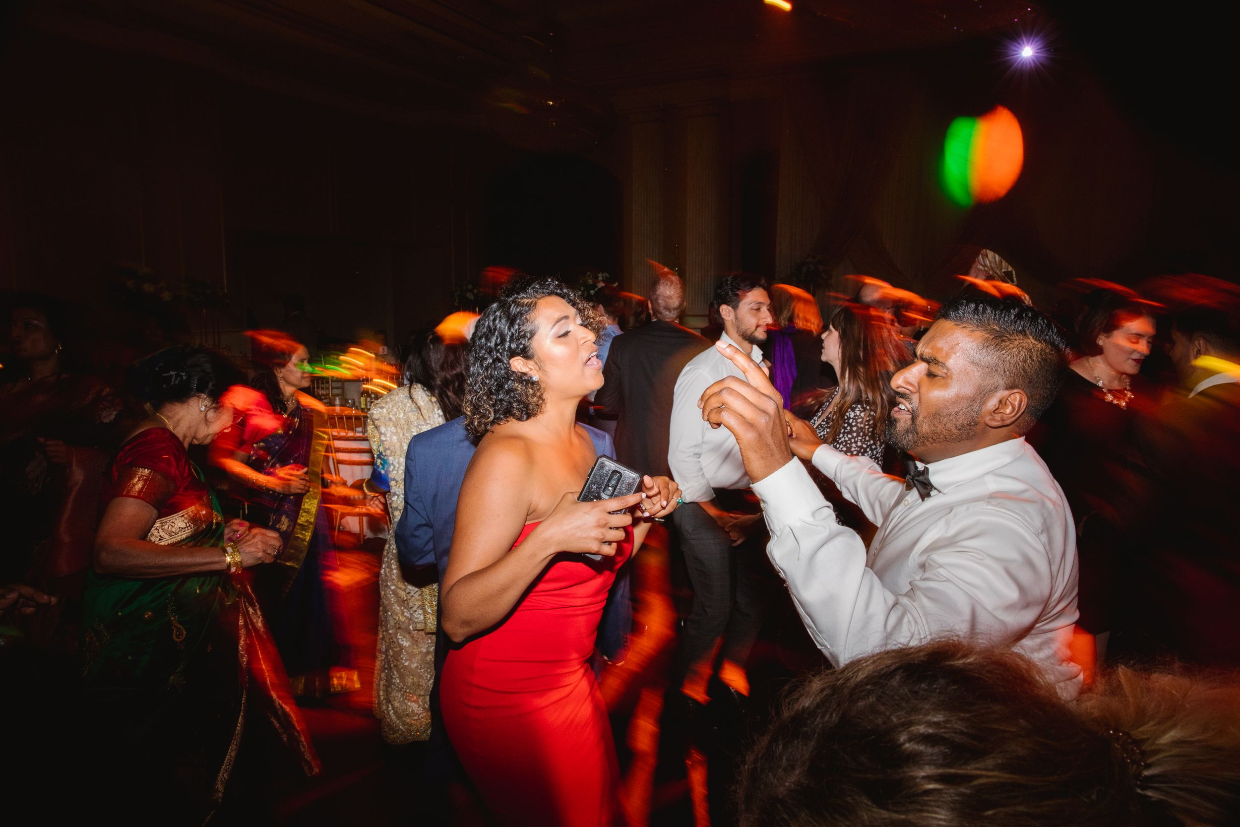 wedding guests dancing and singing with red lights