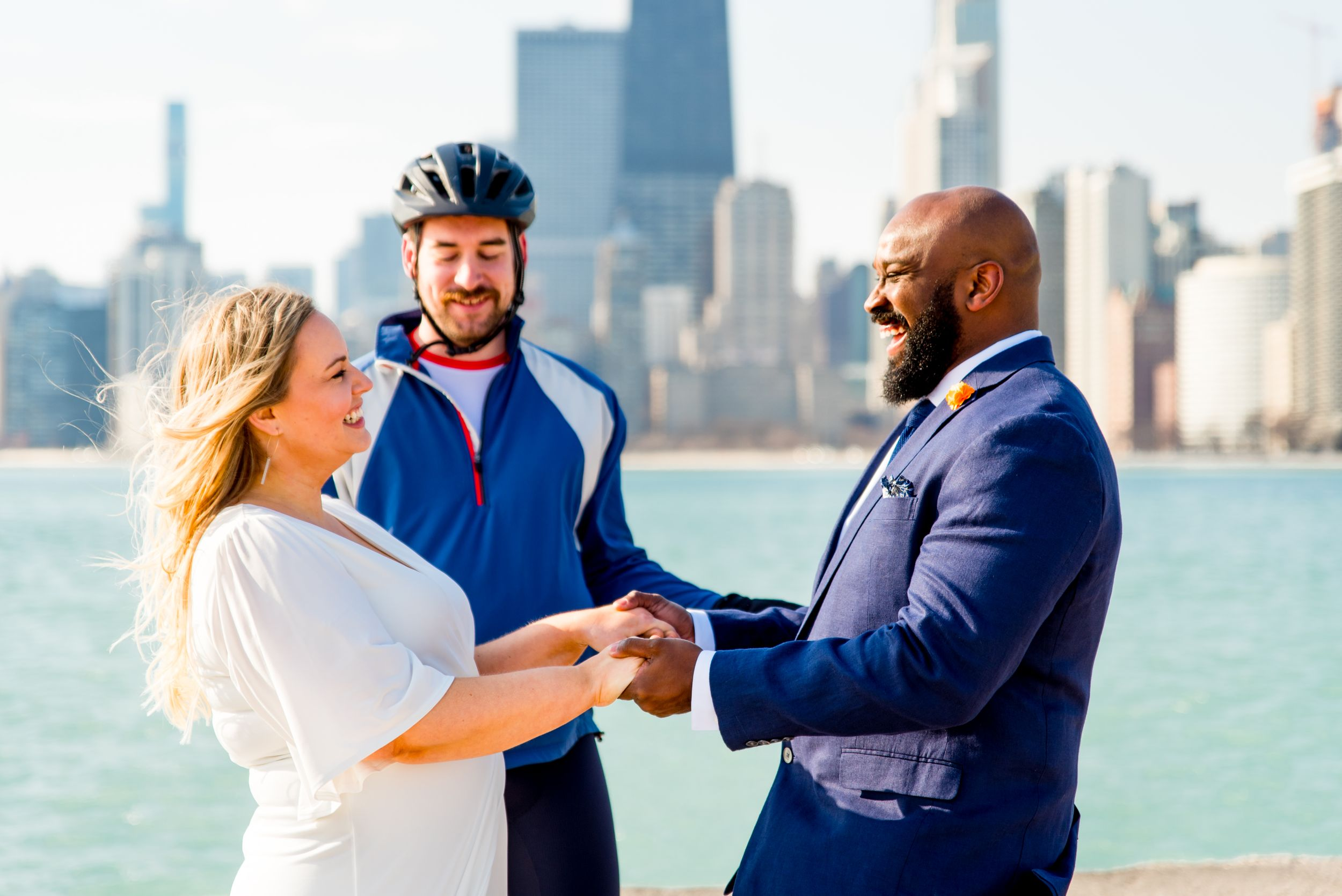 man and woman laughing holding hands as friend in biking outfit marries them at north avenue beach elopement