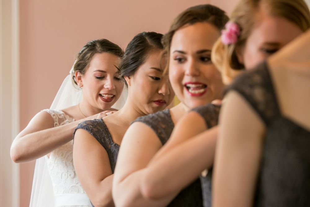 Natalie and her bridesmaids help each other with their dresses before wedding at the Springdale House in Springdale, SC