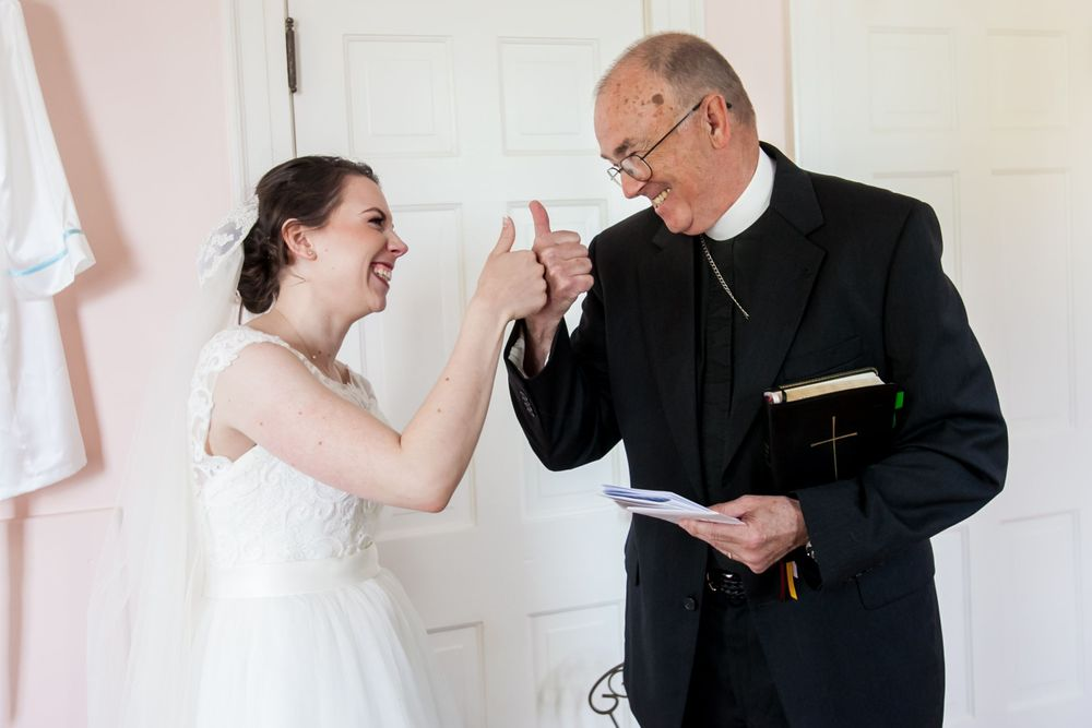 Bride Natalie and her priest fist bump before her wedding at the Springdale House in Springdale, SC