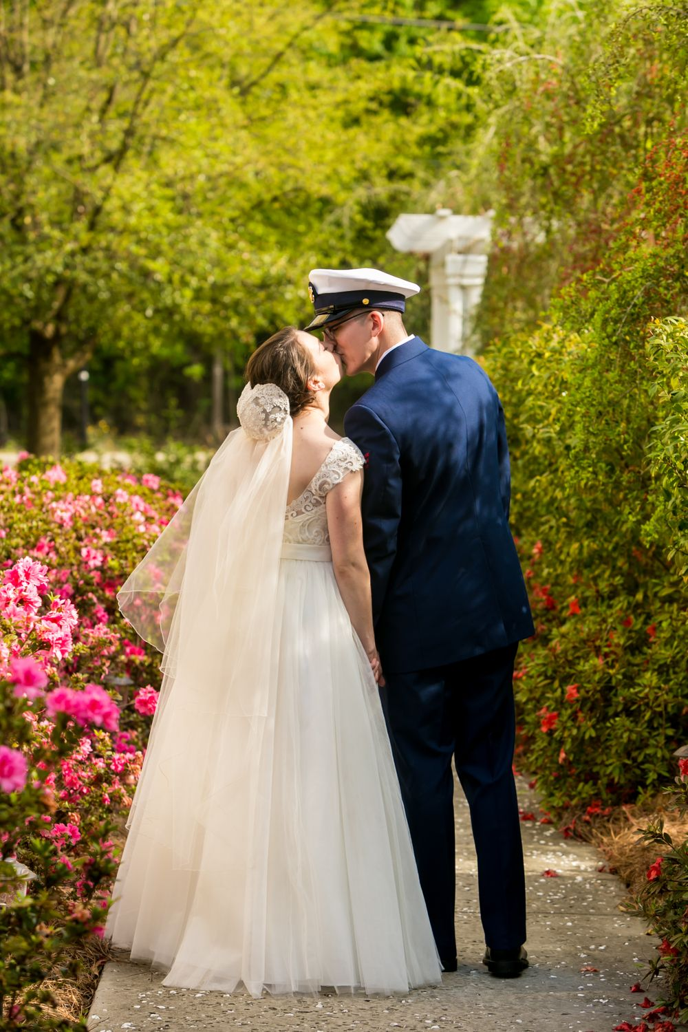 Bride Natalie and groom Ross kiss while walking through the gardens after their wedding at the Springdale House