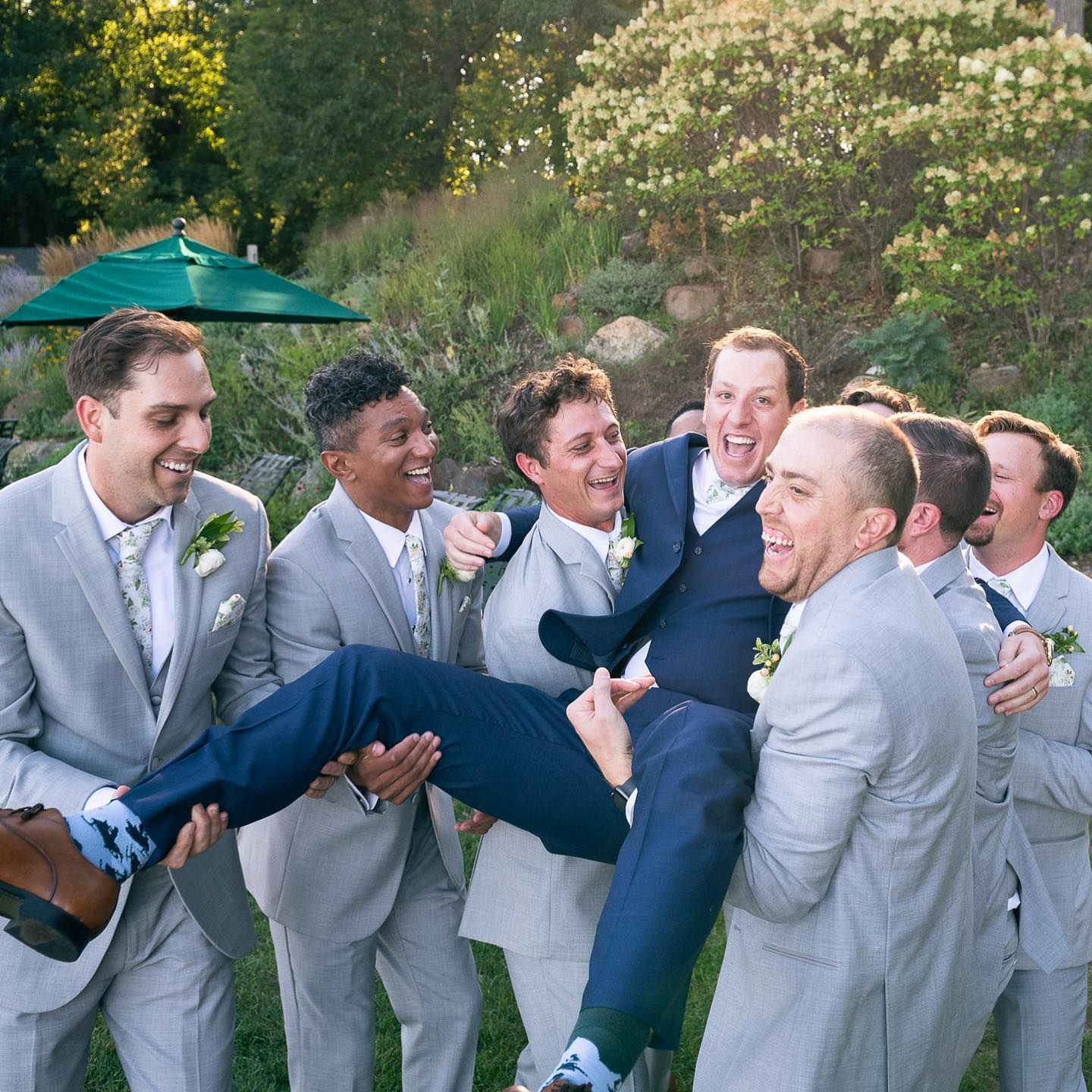groomsmen throwing groom up in the air at chenequa country club