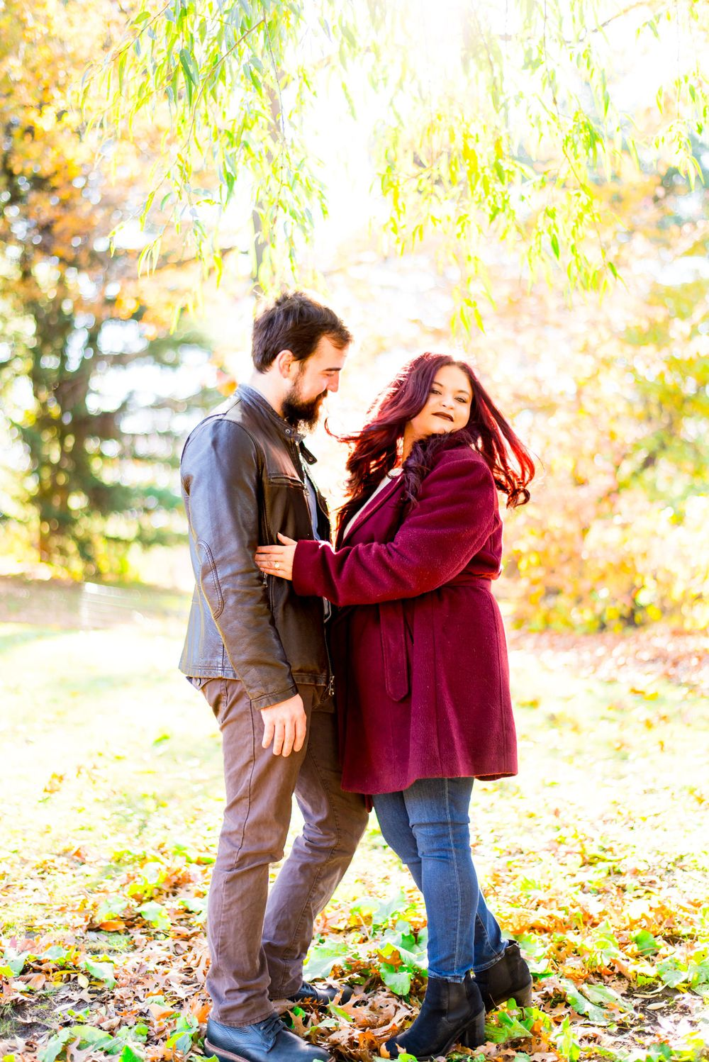 woman in red jacket flips her long red hair under yellow tree at sunrise in Central Park while fiance hugs her