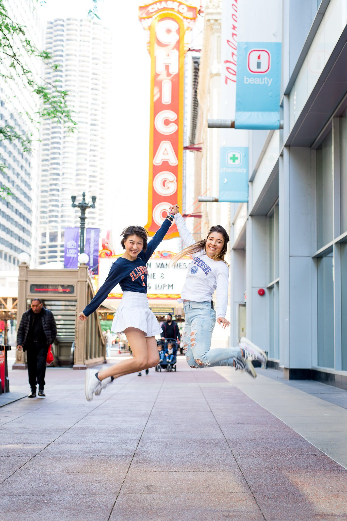 two senior girls jumping in front of the Chicago Theater sign for Chicago senior pictures