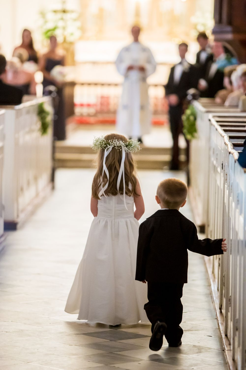 Flower girl and ring bearer walk down the aisle during a wedding at St. Philips Church in Charleston, SC