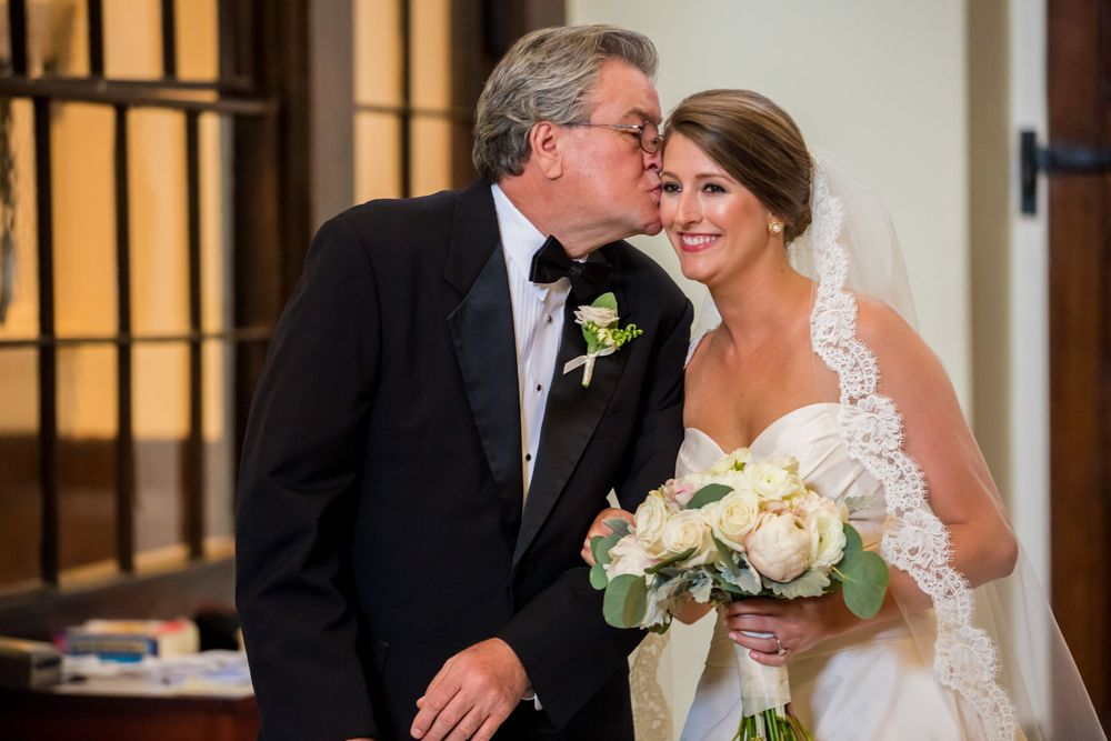 Ashley's father kisses her before walking down the aisle during their wedding at St. Philips Church in Charleston, SC