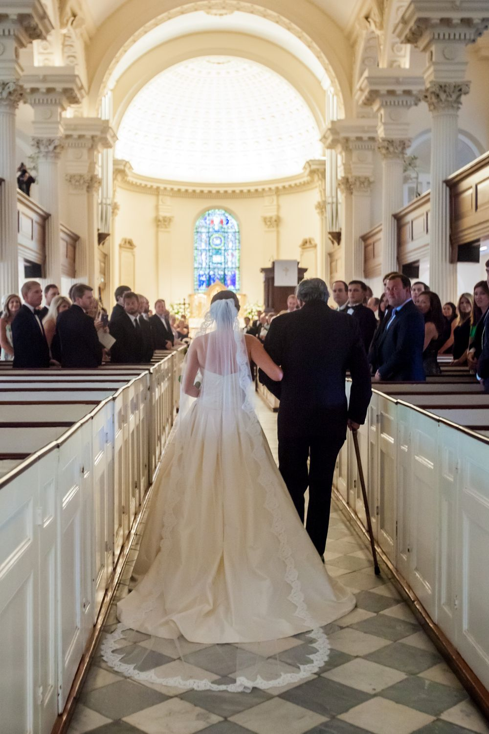 Bride Ashley and her father walk down the aisle during their wedding at St. Philips Church in Charleston, SC