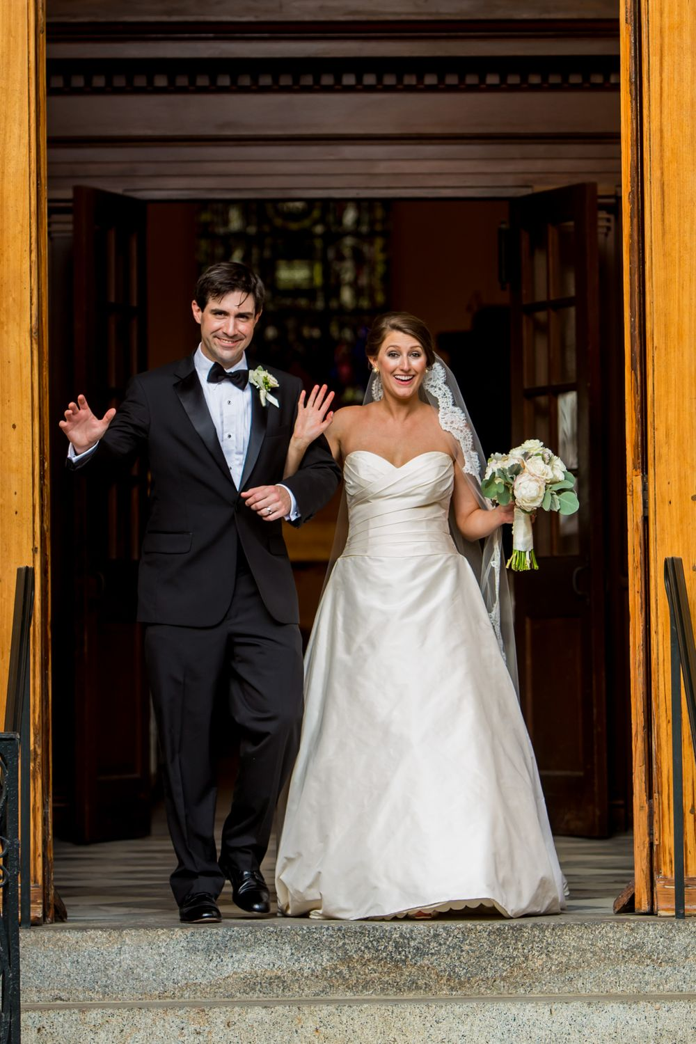 Bride Ashley and groom Ben exit their wedding at St. Philips Church in Charleston, SC