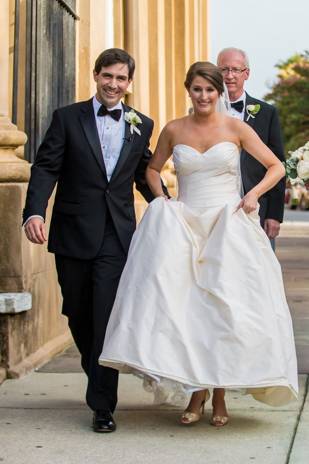 Ashley and Ben walk down the street after their wedding at St. Philips Church in Charleston, SC