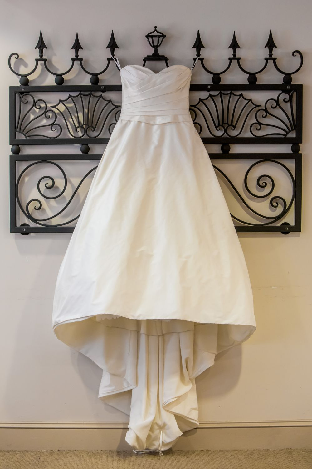 Ashley's bridal gown hangs before a wedding at St. Philips Church in Charleston, SC