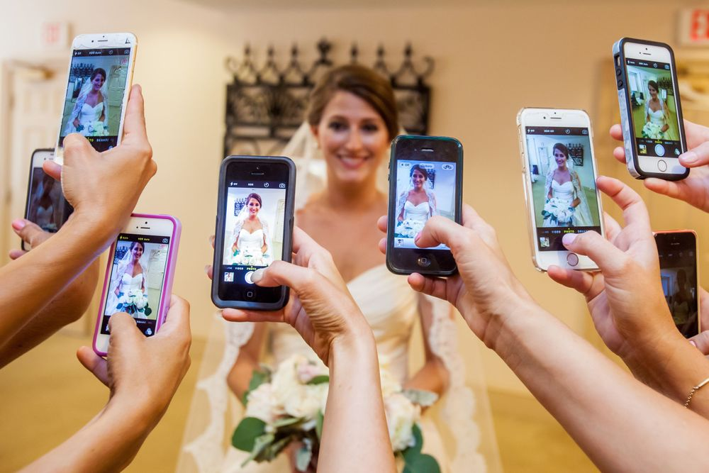 Ashley's bridesmaids take her photo with their smart phones before her wedding at St. Philips Church in Charleston, SC