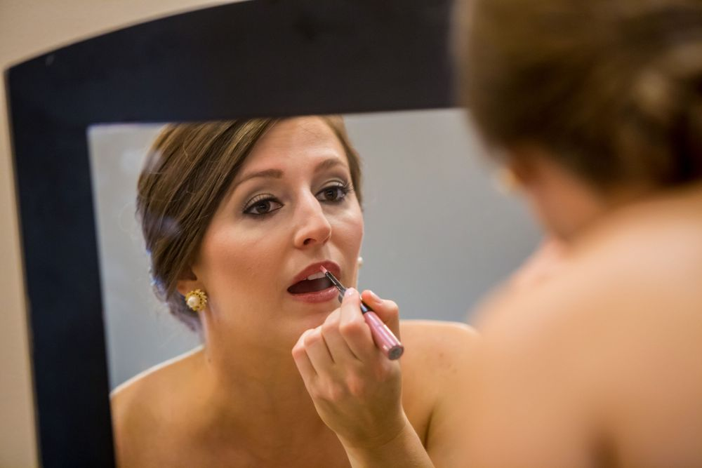 Bride Ashley puts on her makeup in a mirror before her wedding at St. Philips Church in Charleston, SC