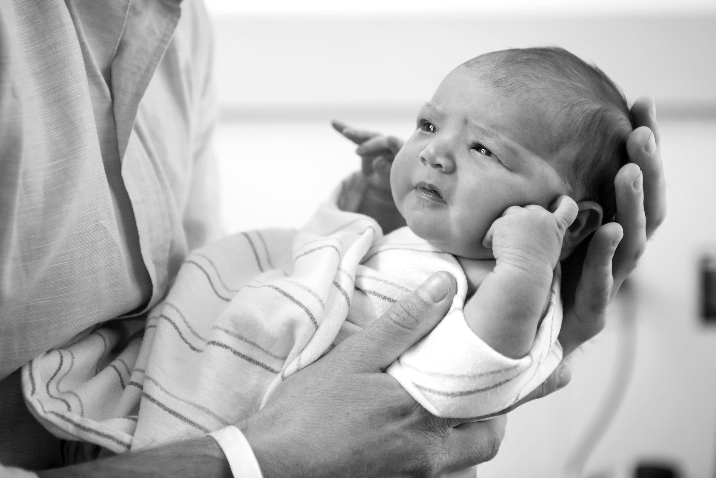 Newborn baby held in father's hands. Captured in a Fresh 48 Documentary Session by Heidi Harting Photography in Plymouth