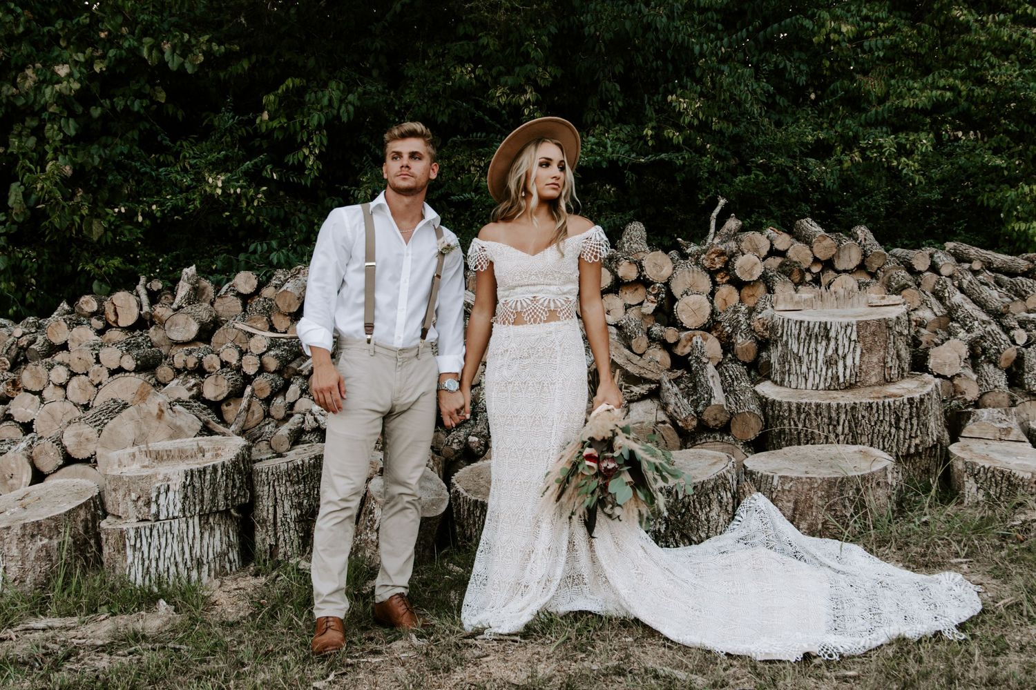 Couple holding hands in front of a pile of logs during their Smoky Mountains elopement