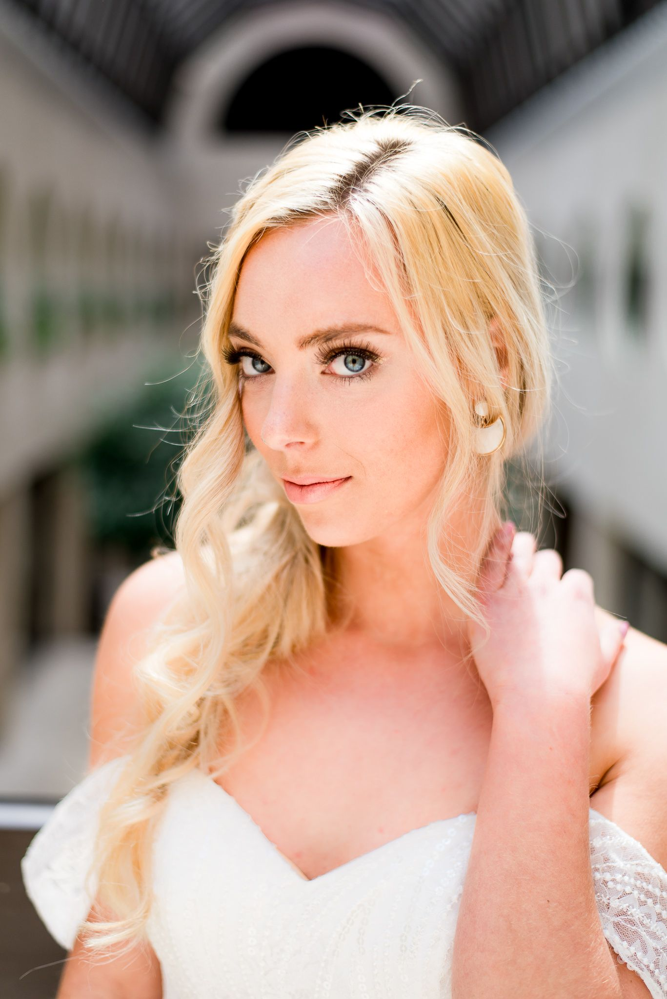 blue eyed blonde bride looks into camera and puts her hand on her neck
