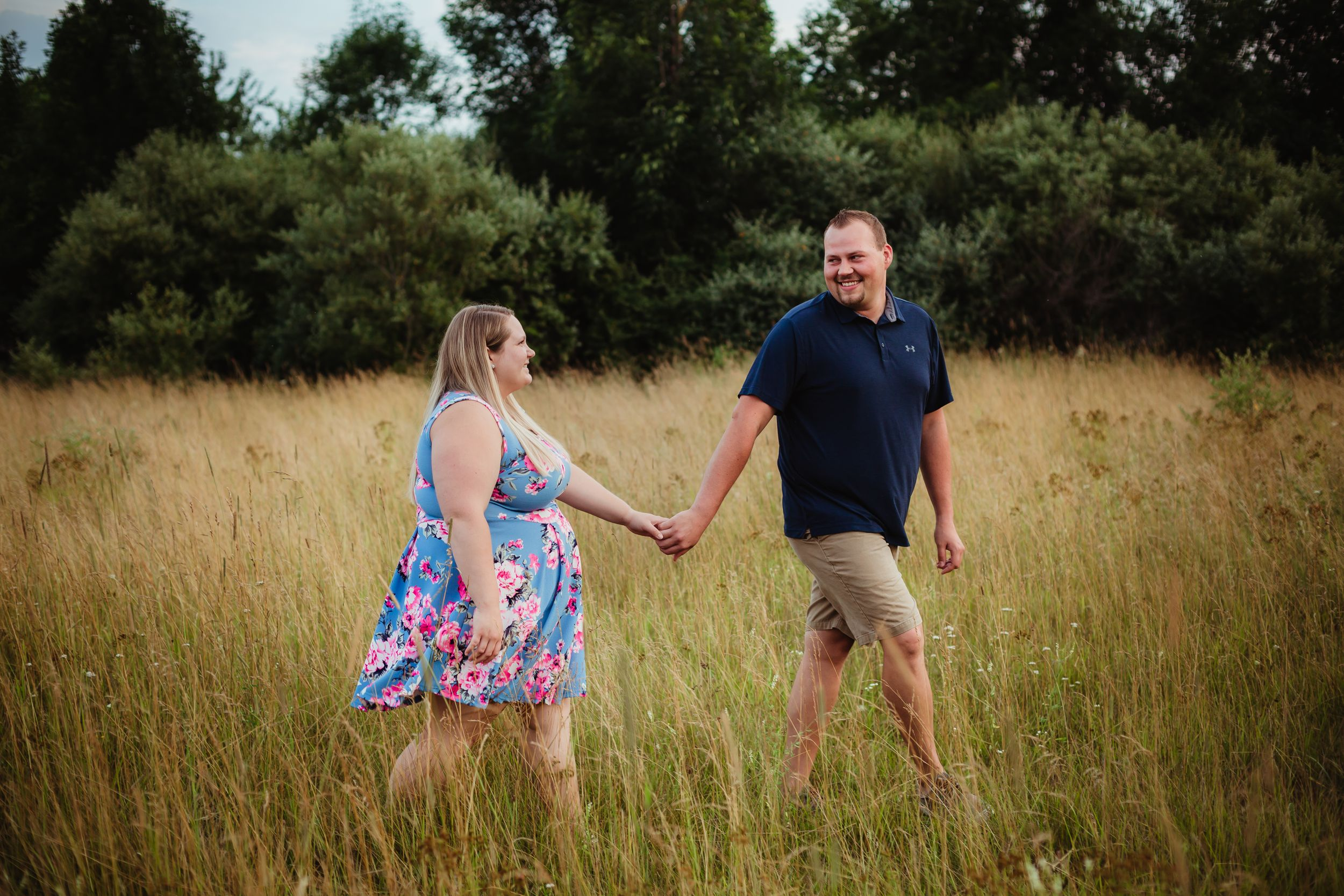 Photo of an engaged couple holding hands walking through a field smiling at each other.
