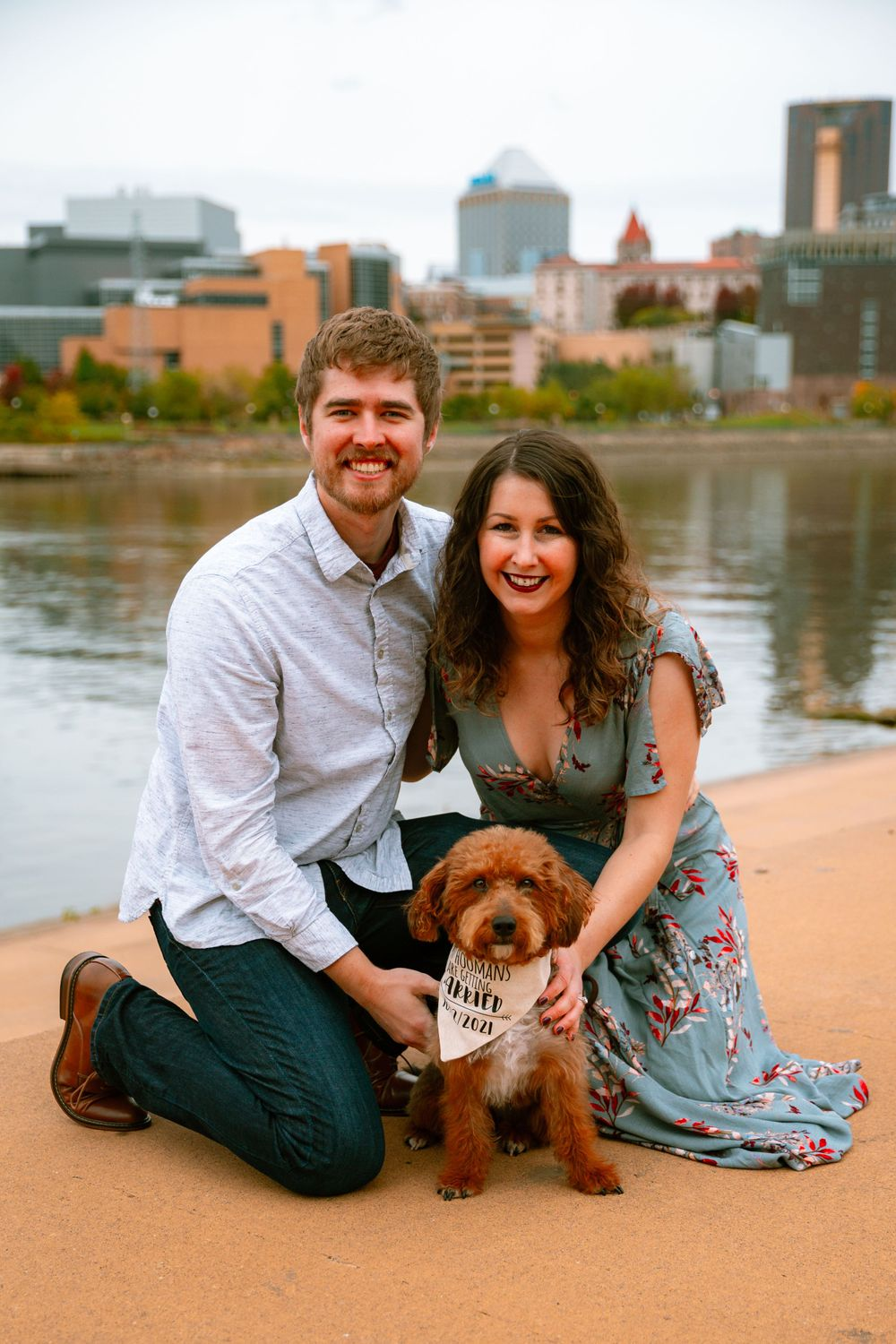 engaged couple with dog with skyline in the background