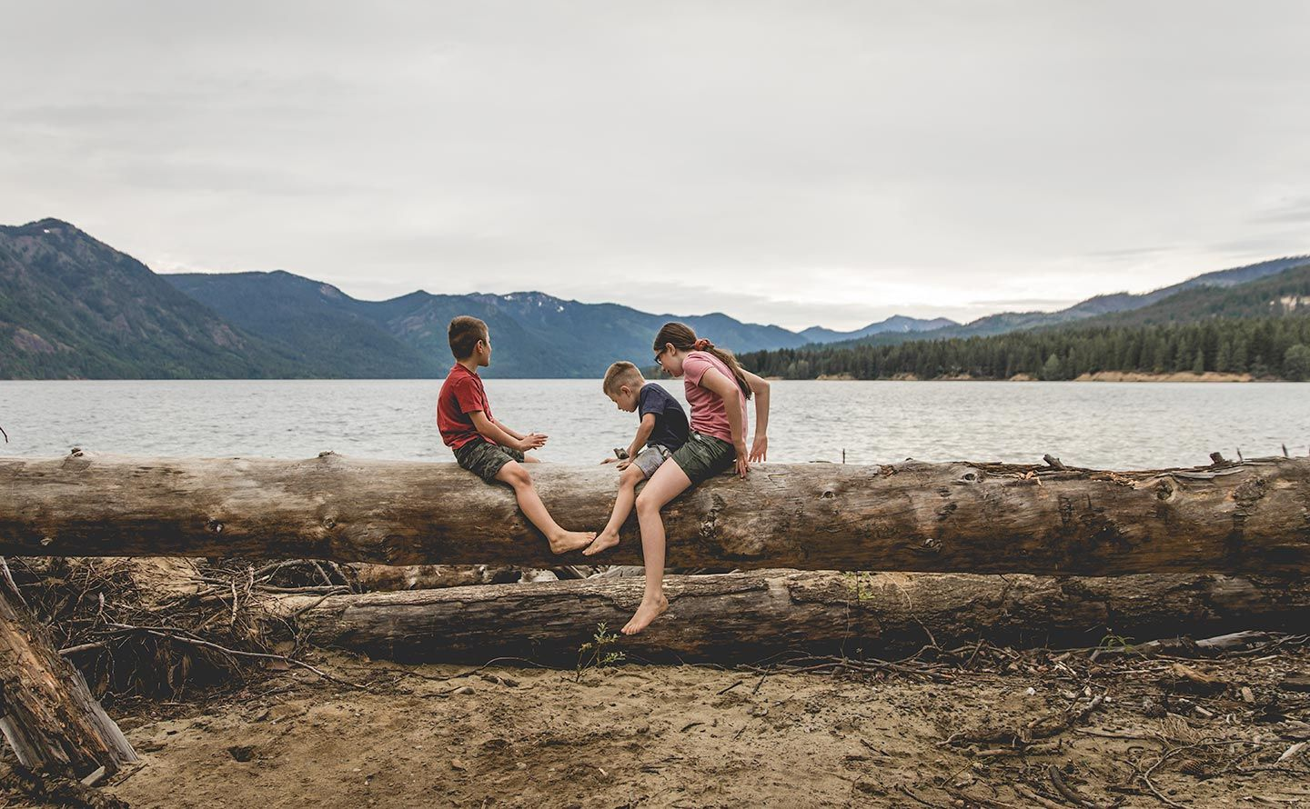 three siblings sitting on log by Cle Elum Lake