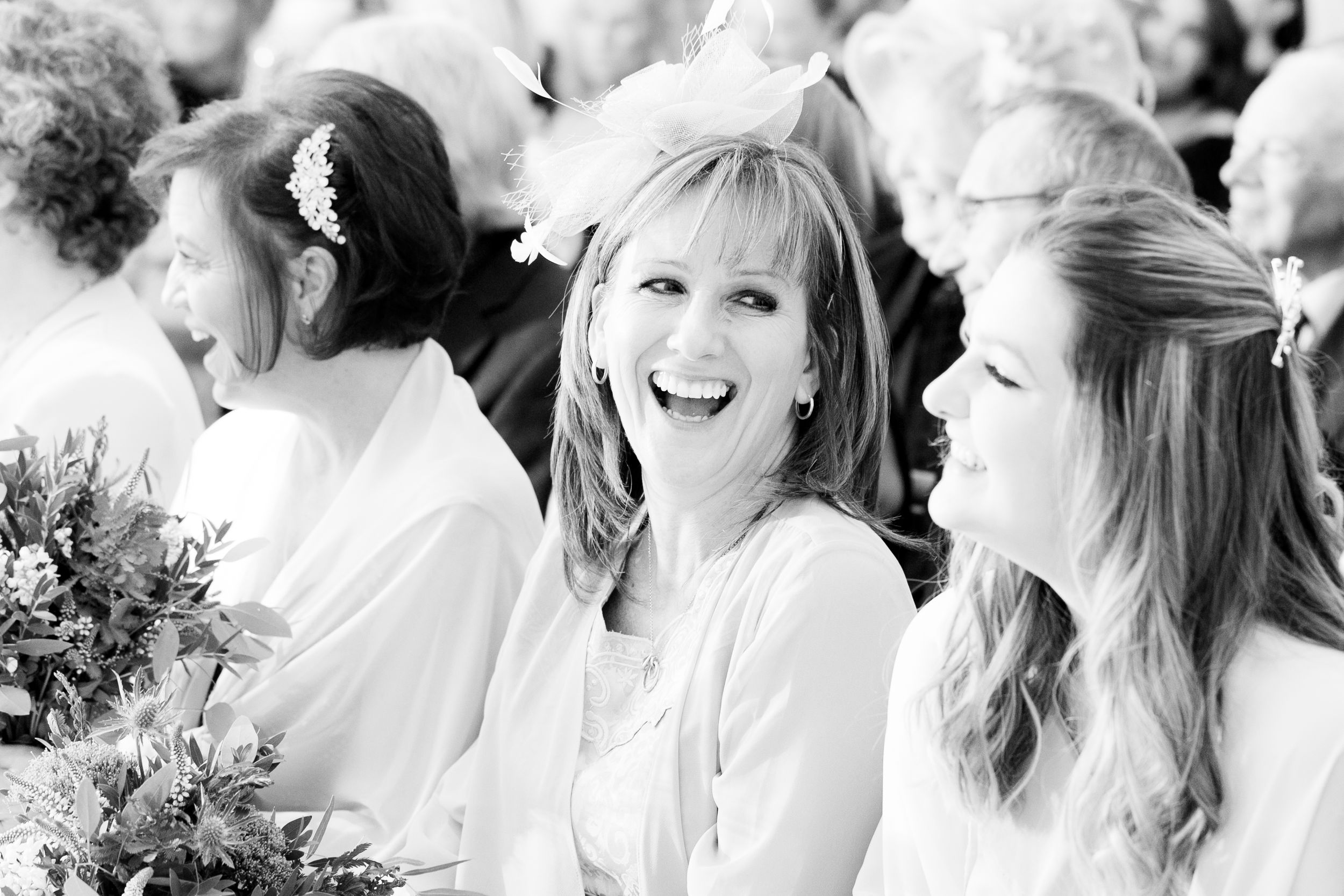 Black & white image of a guest laughing during a wedding ceremony - Wedding Photography