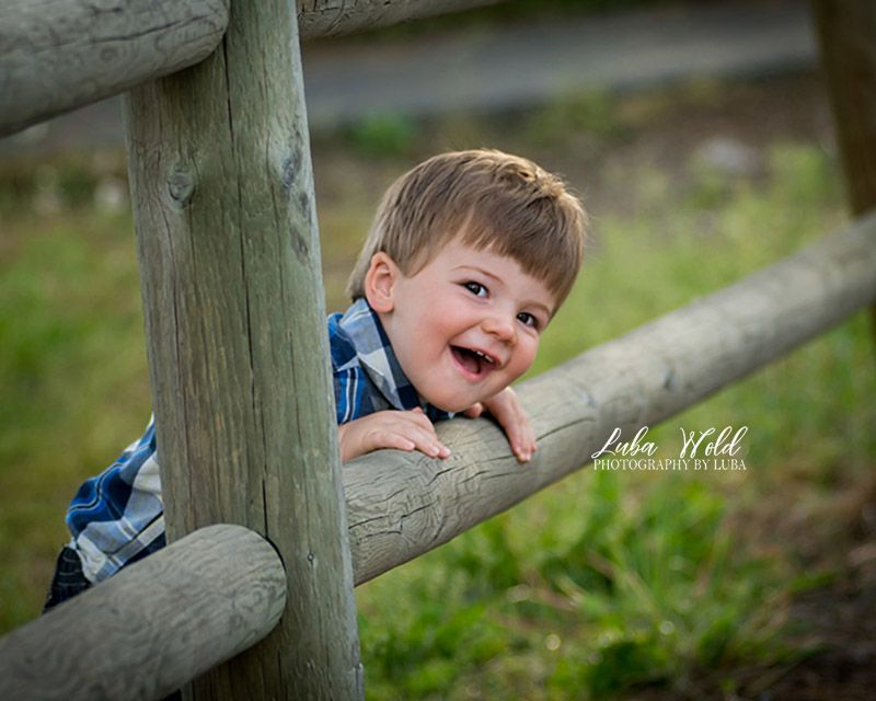 toddler boy picking through fence smiling photographer luba wold spokane