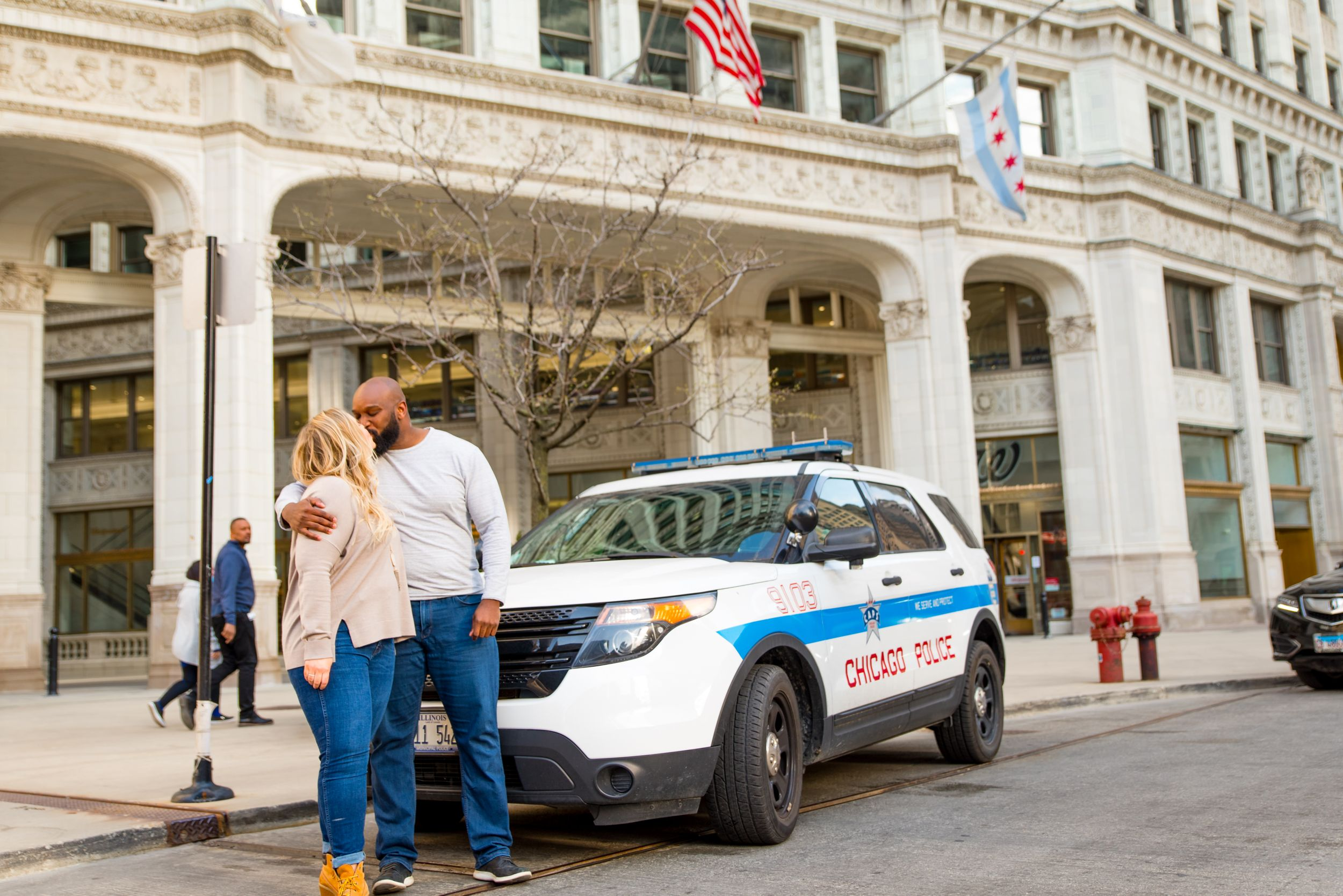 man and woman kissing in front of cop car at Wrigley Building for engagement photos in Chicago